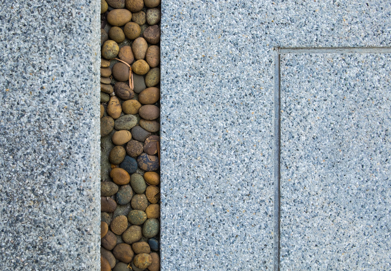 stone material, no people, day, large group of objects, textured, outdoors, stack, pebble