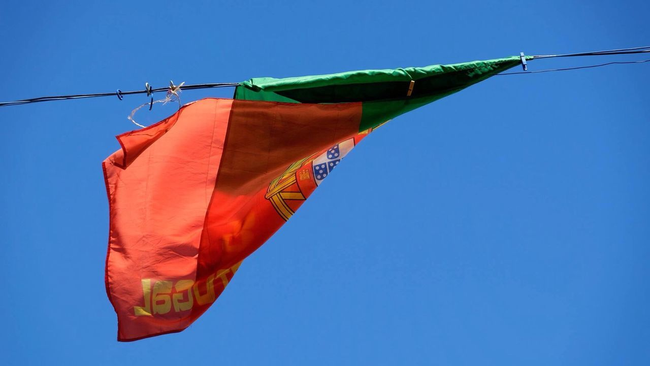 clear sky, blue, low angle view, copy space, hanging, red, flag, part of, day, rope, outdoors, multi colored, identity, cropped, close-up, yellow, patriotism, no people, sunlight, protection