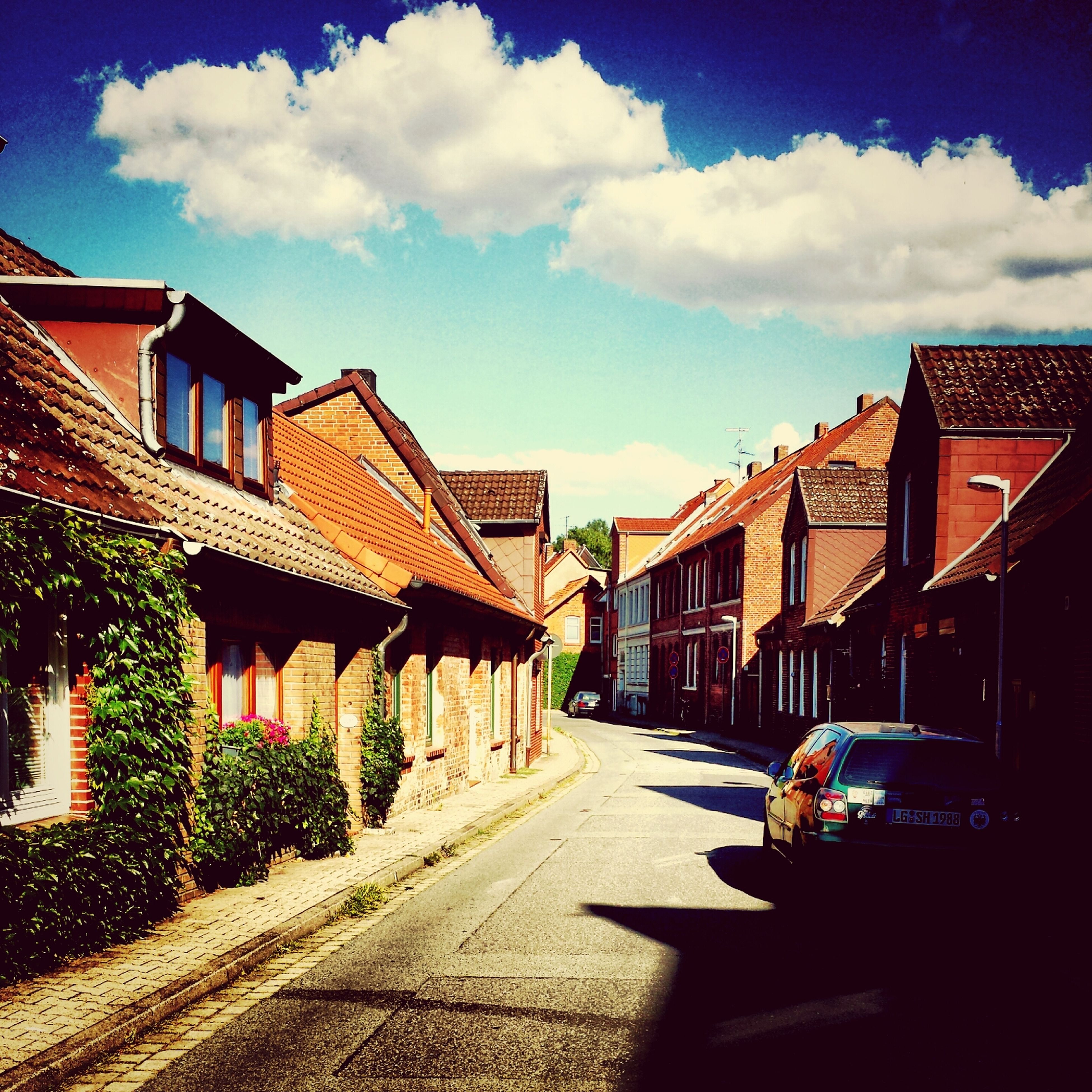 building exterior, architecture, built structure, house, sky, residential structure, the way forward, residential building, street, sunlight, roof, road, town, diminishing perspective, cloud, city, cobblestone, residential district, outdoors, vanishing point