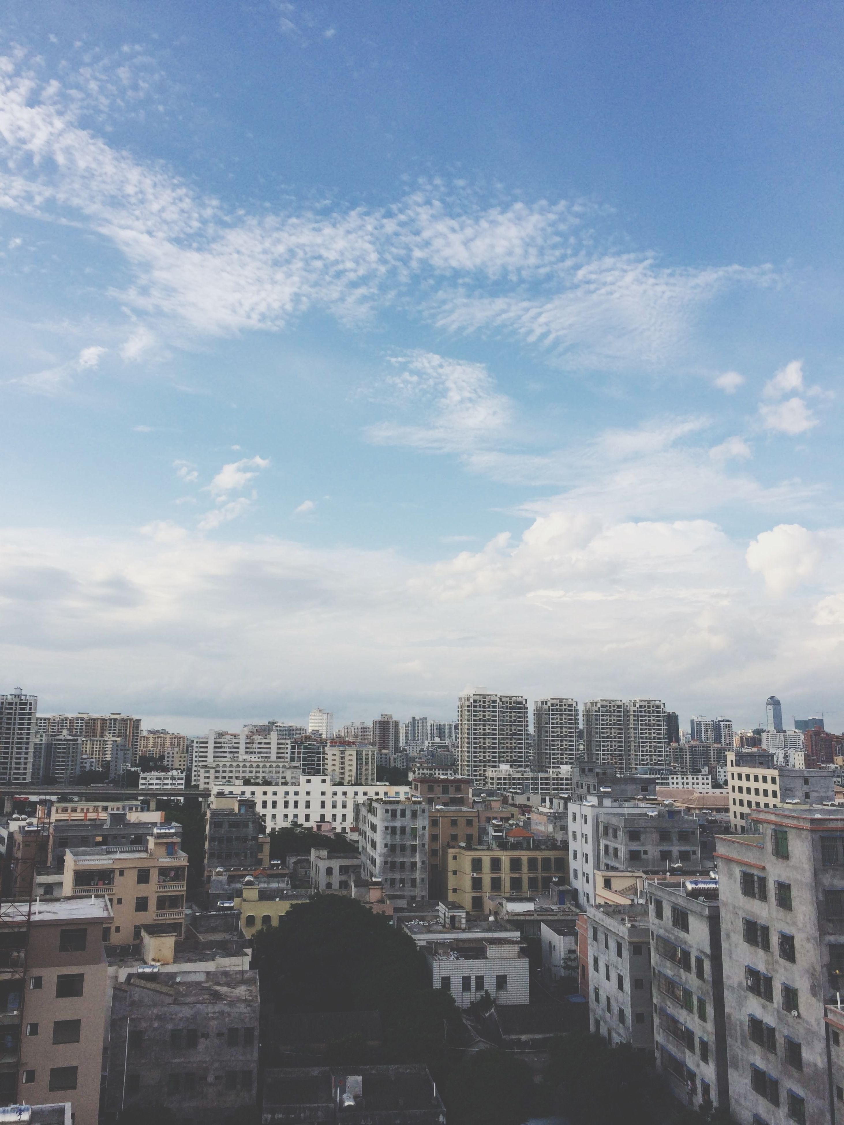 building exterior, architecture, built structure, city, cityscape, sky, residential district, crowded, residential building, residential structure, cloud - sky, high angle view, cloud, blue, day, outdoors, no people, city life, house, building