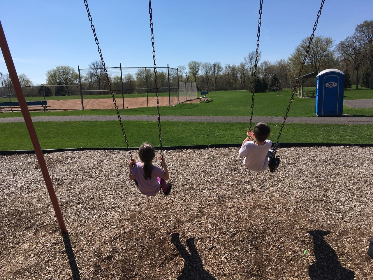 Kids On Swing Swinging Swings Playground Park Playtime Sunny Day Blue Toilet Green Grass Baseball Field Kids Boy Girl Children Playing