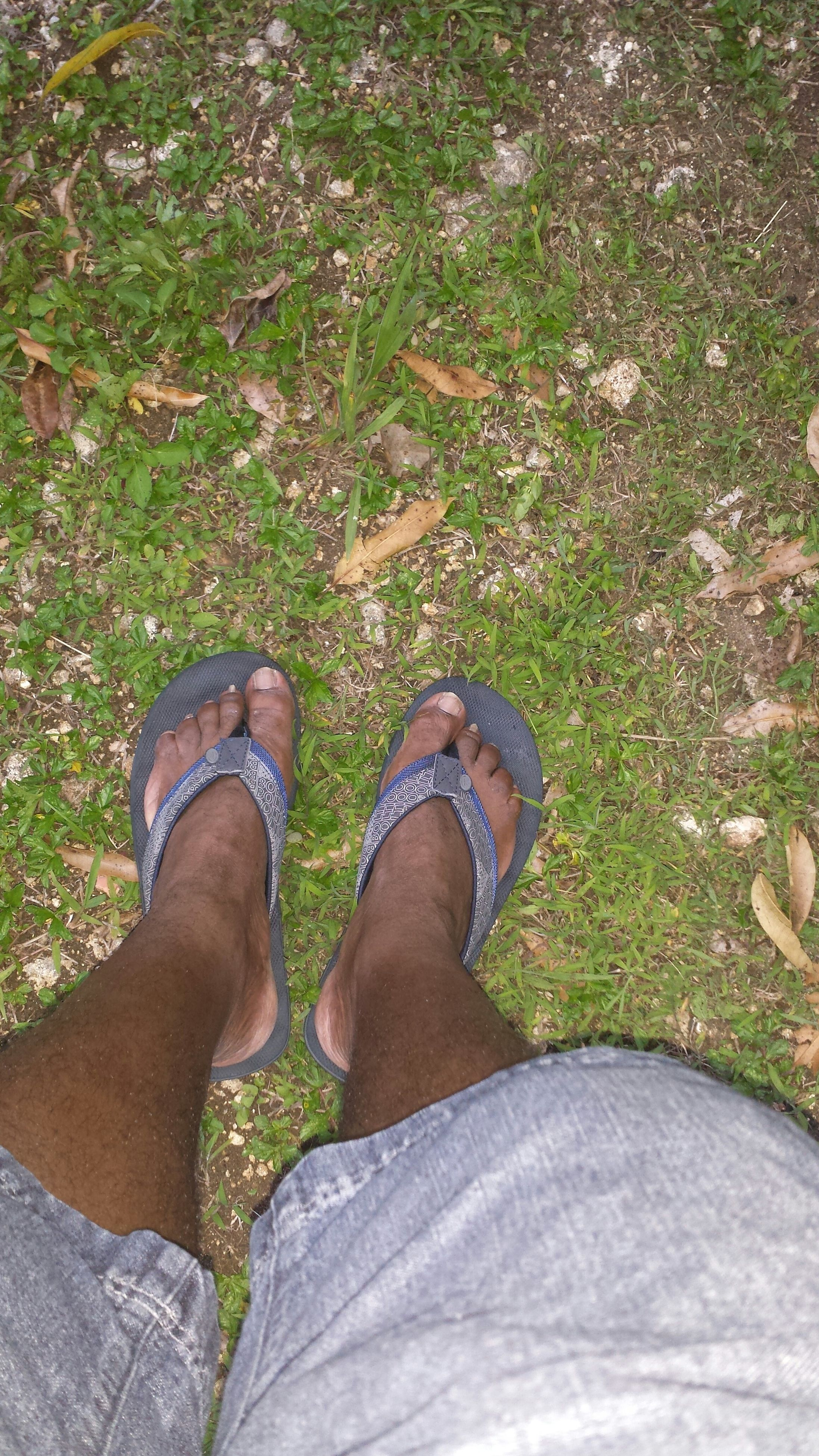 low section, person, personal perspective, shoe, lifestyles, leisure activity, human foot, standing, high angle view, jeans, footwear, men, relaxation, casual clothing, barefoot, grass