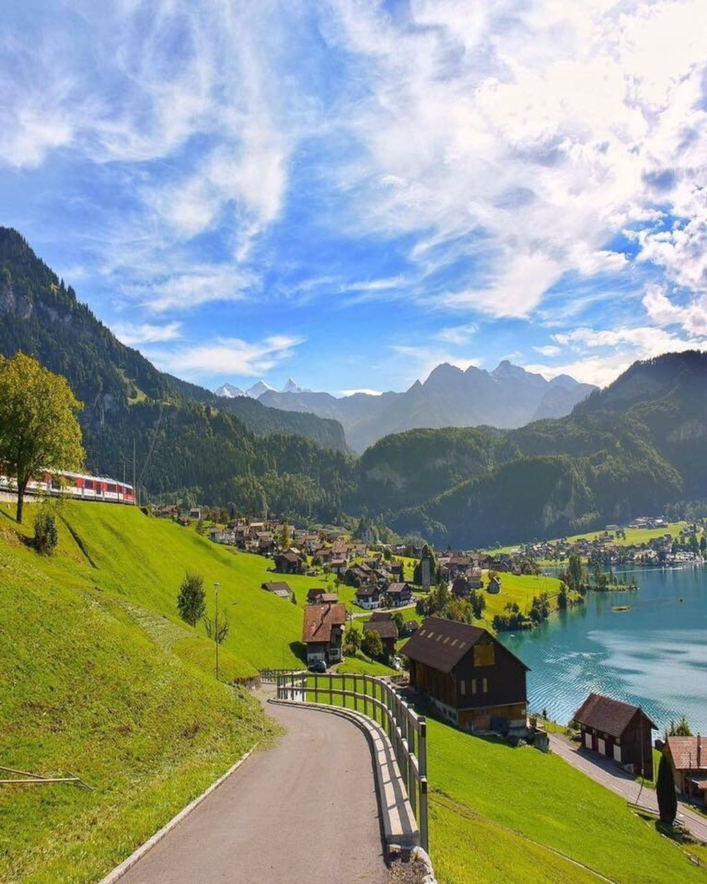 mountain, mountain range, road, scenics, nature, outdoors, transportation, cloud - sky, sky, the way forward, built structure, day, tranquility, landscape, beauty in nature, architecture, tranquil scene, tree, no people, grass, travel destinations, water, building exterior, winding road