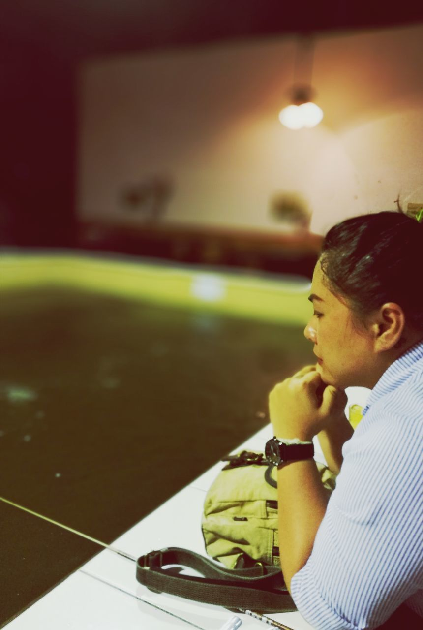 Thoughtful Woman With Hand On Chin Leaning On Pool Table