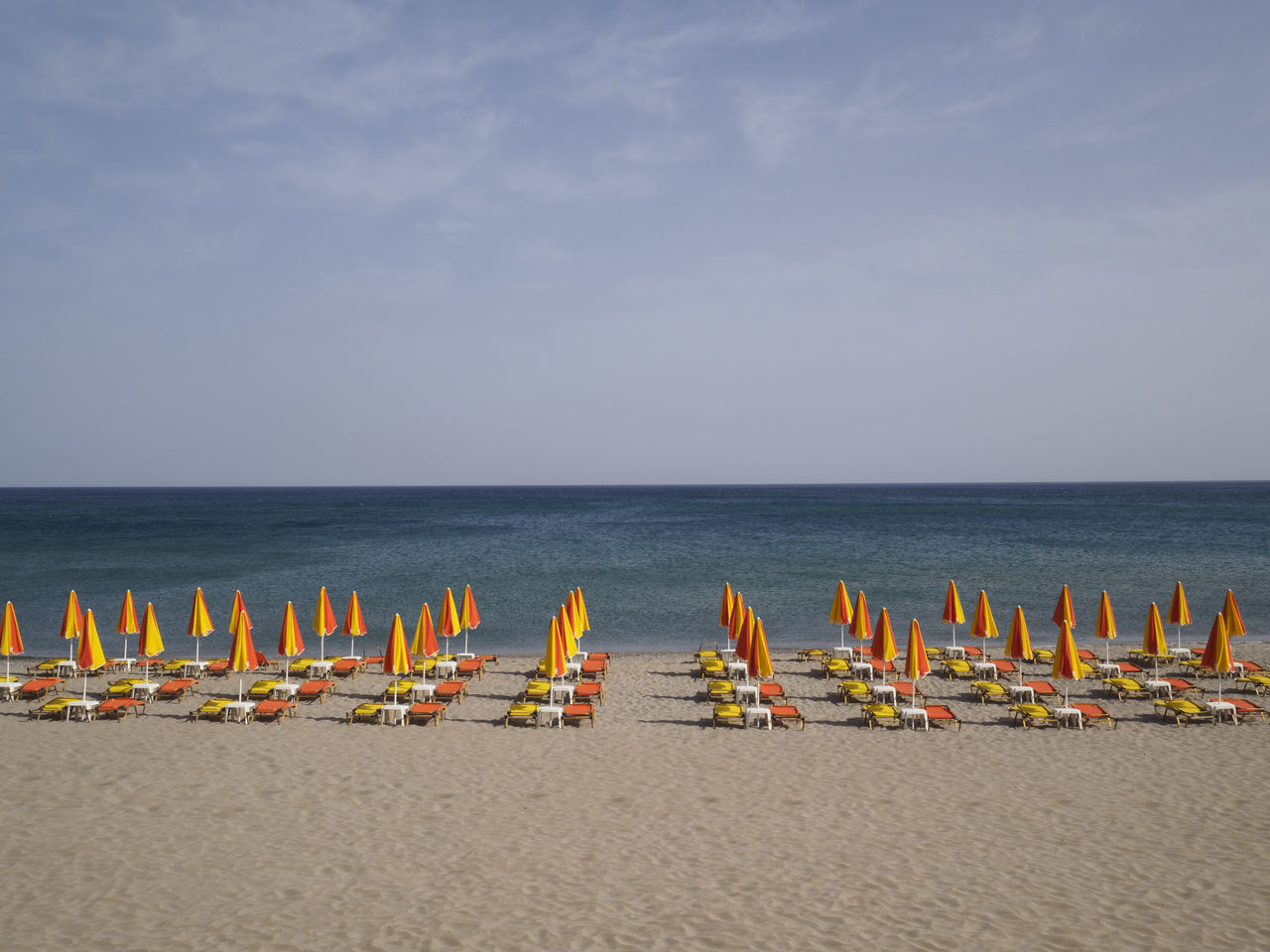 beach at Rethymno Crete with the umbrellas and loungers set out for the day Beach Beach Umbrella In A Row Protection Sand Sea Summer Sun Lounger Tranquility Umbrella Vacations