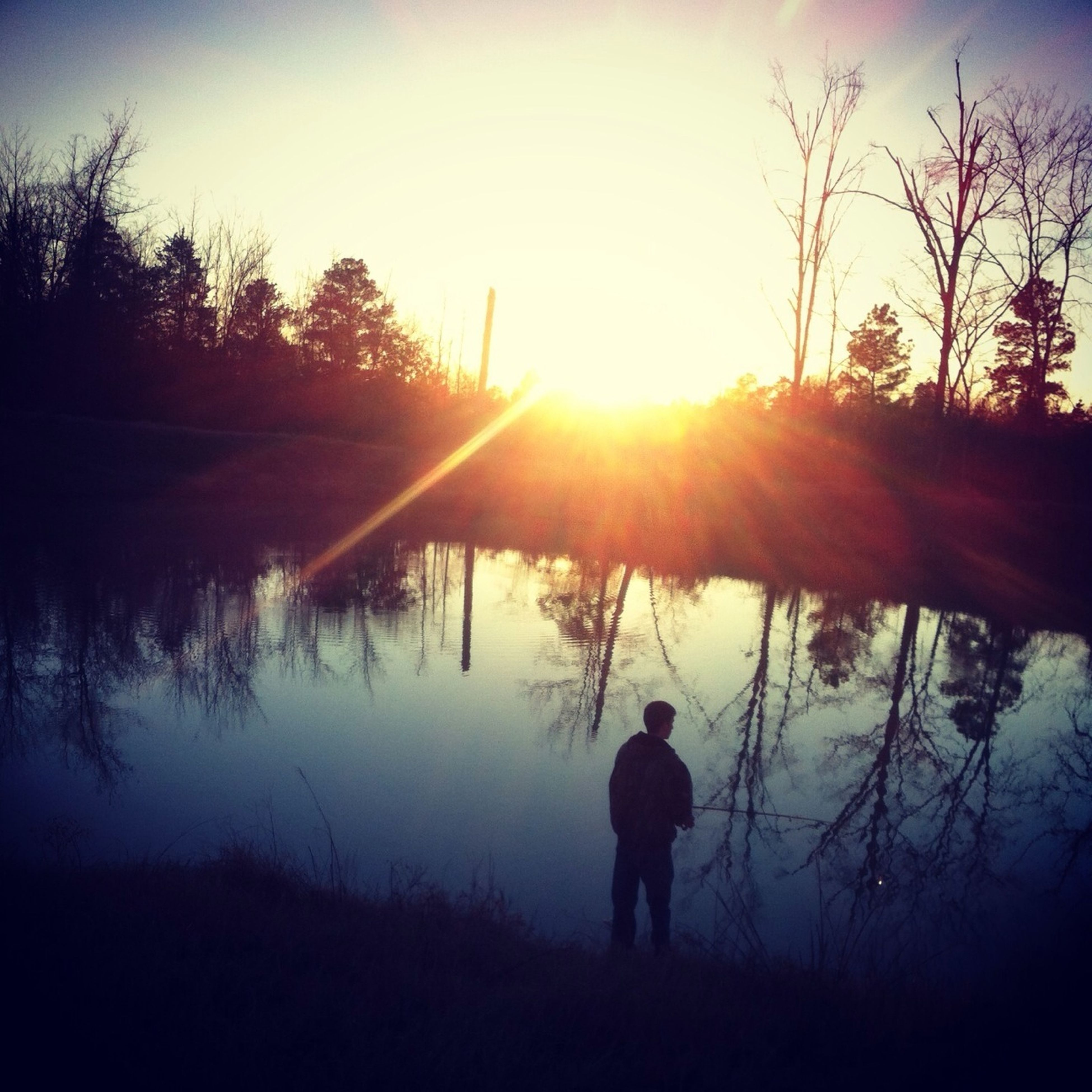sun, sunset, silhouette, lifestyles, leisure activity, tranquil scene, tree, water, tranquility, rear view, lake, beauty in nature, reflection, sunlight, men, standing, scenics, nature
