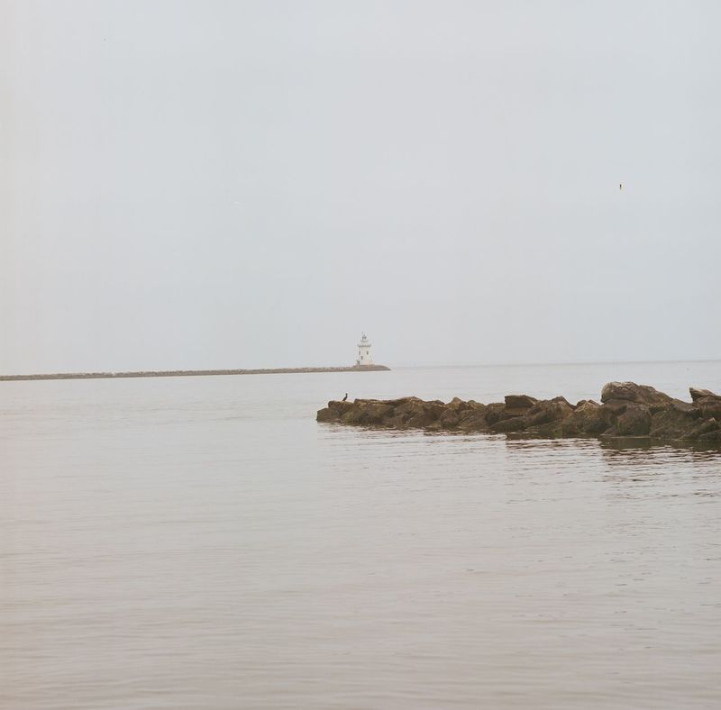 A grey day on the Connecticut shore looking out towards a lighthouse. Beach Calm Clouds Clouds And Sky Coastline Distant Escapism Getting Away From It All Grey Grey Sky Horizon Over Water Lighthouse Ocean Outdoors Relaxing Moments Rippled Sea Seascape Shore Tranquil Scene Vacations Water