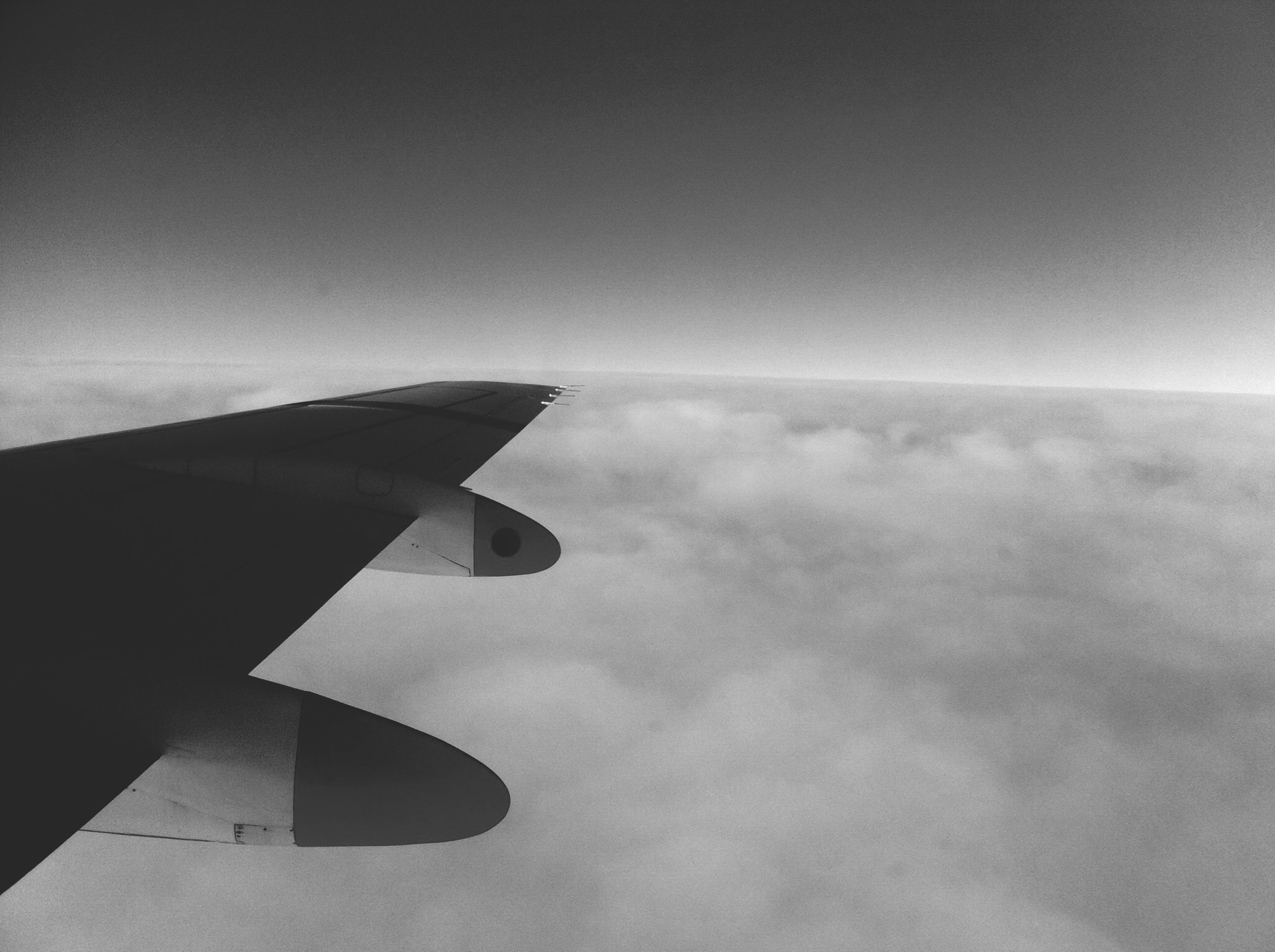 airplane, air vehicle, flying, aircraft wing, part of, sky, cropped, transportation, mode of transport, mid-air, low angle view, cloud - sky, travel, copy space, aerial view, outdoors, no people, day, cloud, journey