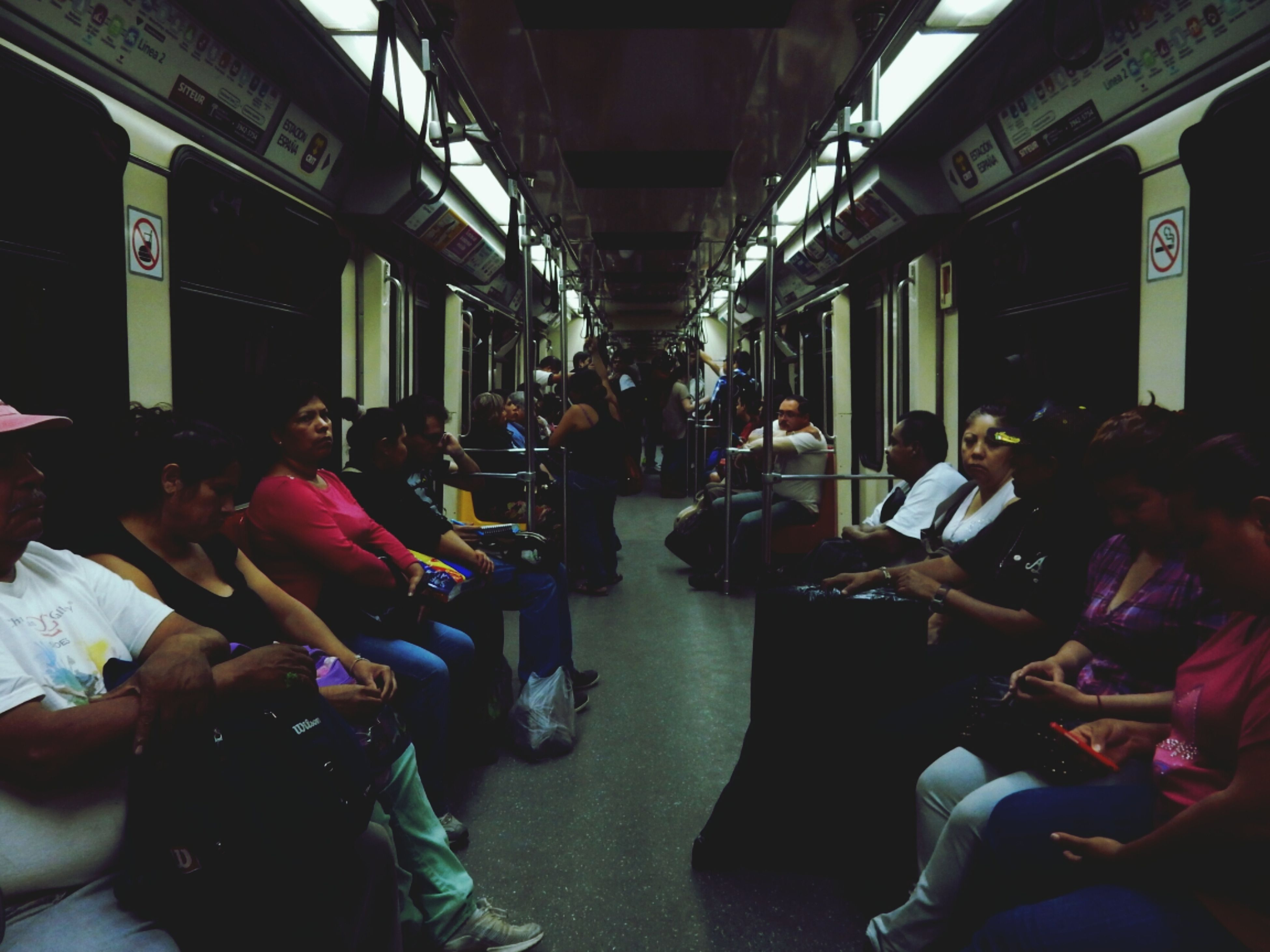 men, large group of people, person, lifestyles, indoors, sitting, leisure activity, medium group of people, transportation, city life, illuminated, chair, group of people, travel, mode of transport, restaurant, incidental people, bus, city