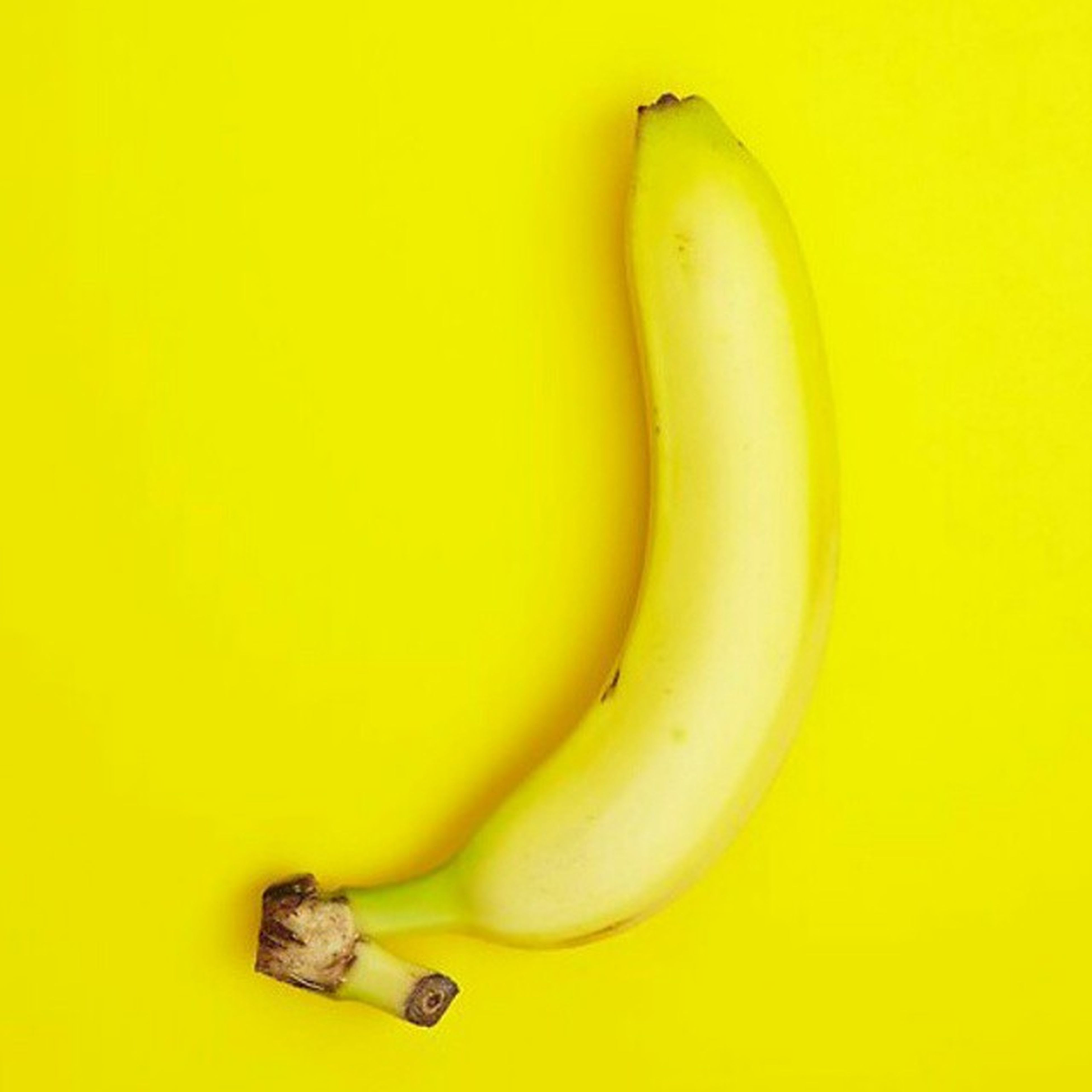 yellow, indoors, still life, studio shot, close-up, single object, white background, healthy eating, food and drink, fruit, banana, wall - building feature, no people, table, food, two objects, copy space, high angle view, freshness, wall