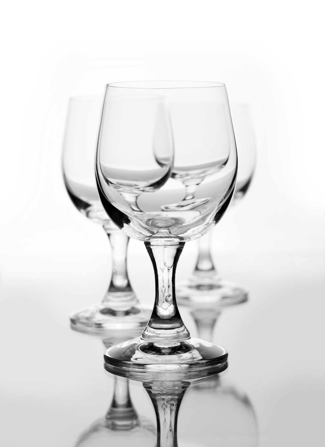 Three empty wine glasses on white, one by one blurred behind, objects standing on glass on white background, vertical orientation, nobody. Alcohol Contour Empty Food And Drink Glass No People Stem Stemmed Stemware Studio Shot White Background Wineglass Wineglasses