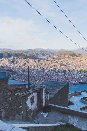 At the top of the Mi Teliferico cable car in La Paz, El Alto - Bolivia Architecture Building Exterior Built Structure Cable Canal City Cityscape Cloud Cloud - Sky Day High Angle View Horizon Over Land Housing Settlement Mountain No People Outdoors Power Line  Residential District Residential Structure River Rooftop Sky Town Water Wide Shot
