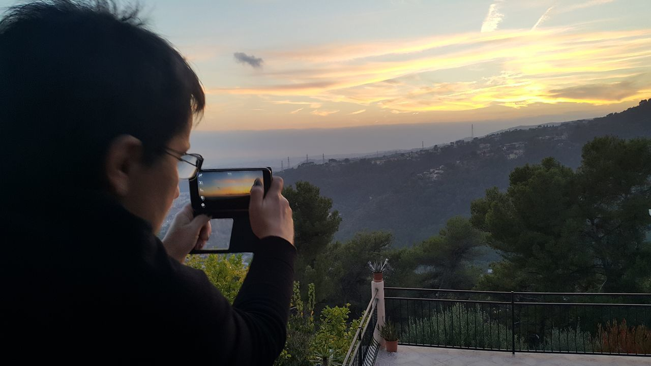 sunset, sky, photographing, real people, one person, cloud - sky, leisure activity, railing, rear view, scenics, lifestyles, women, photography themes, nature, outdoors, camera - photographic equipment, mountain, beauty in nature, water, tree, wireless technology, sea, technology, close-up, day, coin-operated binoculars, young adult