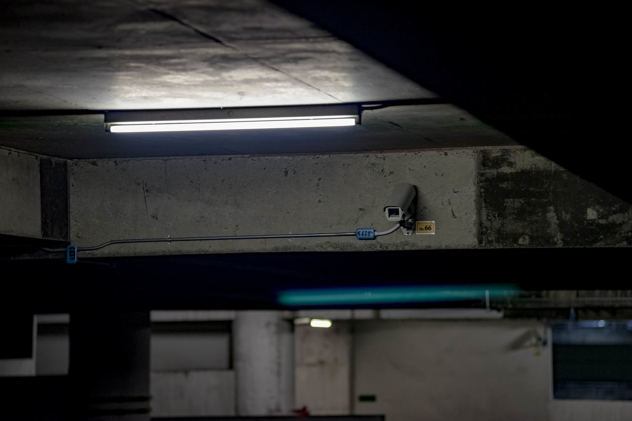 Security Camera On Illuminated Ceiling At Underground Parking Lot
