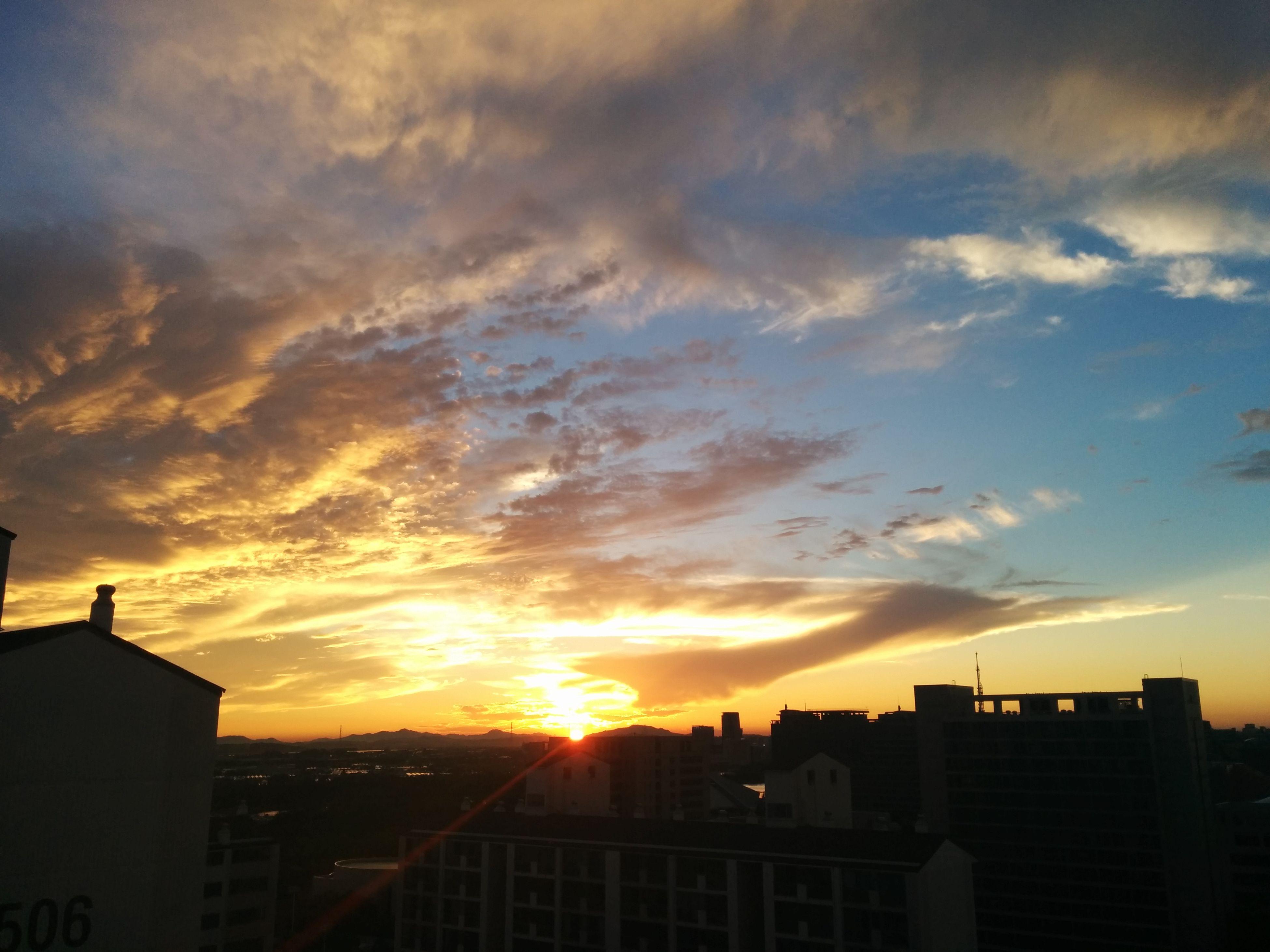 sunset, building exterior, architecture, built structure, sky, silhouette, orange color, cloud - sky, city, sun, cityscape, cloud, residential building, residential structure, building, beauty in nature, sunlight, dramatic sky, scenics, cloudy