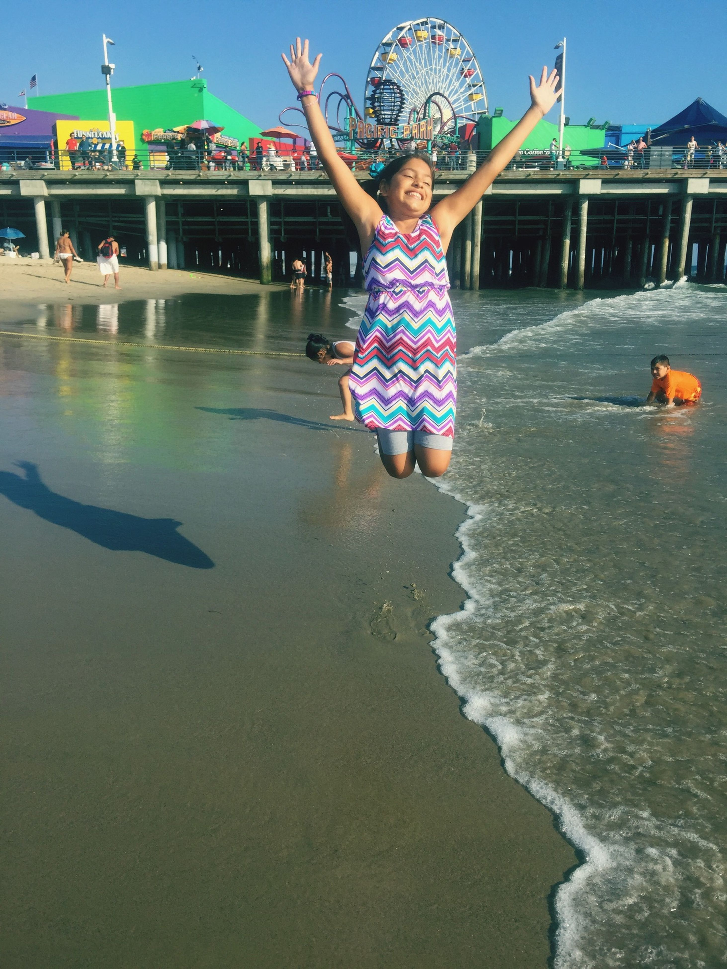full length, lifestyles, leisure activity, person, casual clothing, childhood, water, fun, enjoyment, front view, happiness, elementary age, mid-air, young adult, girls, jumping, standing, boys