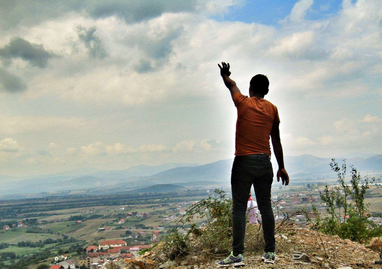 sky, real people, rear view, cloud - sky, leisure activity, standing, casual clothing, lifestyles, mountain, full length, one person, men, outdoors, day, scenics, landscape, nature, beauty in nature, photographing, photography themes, adult, people