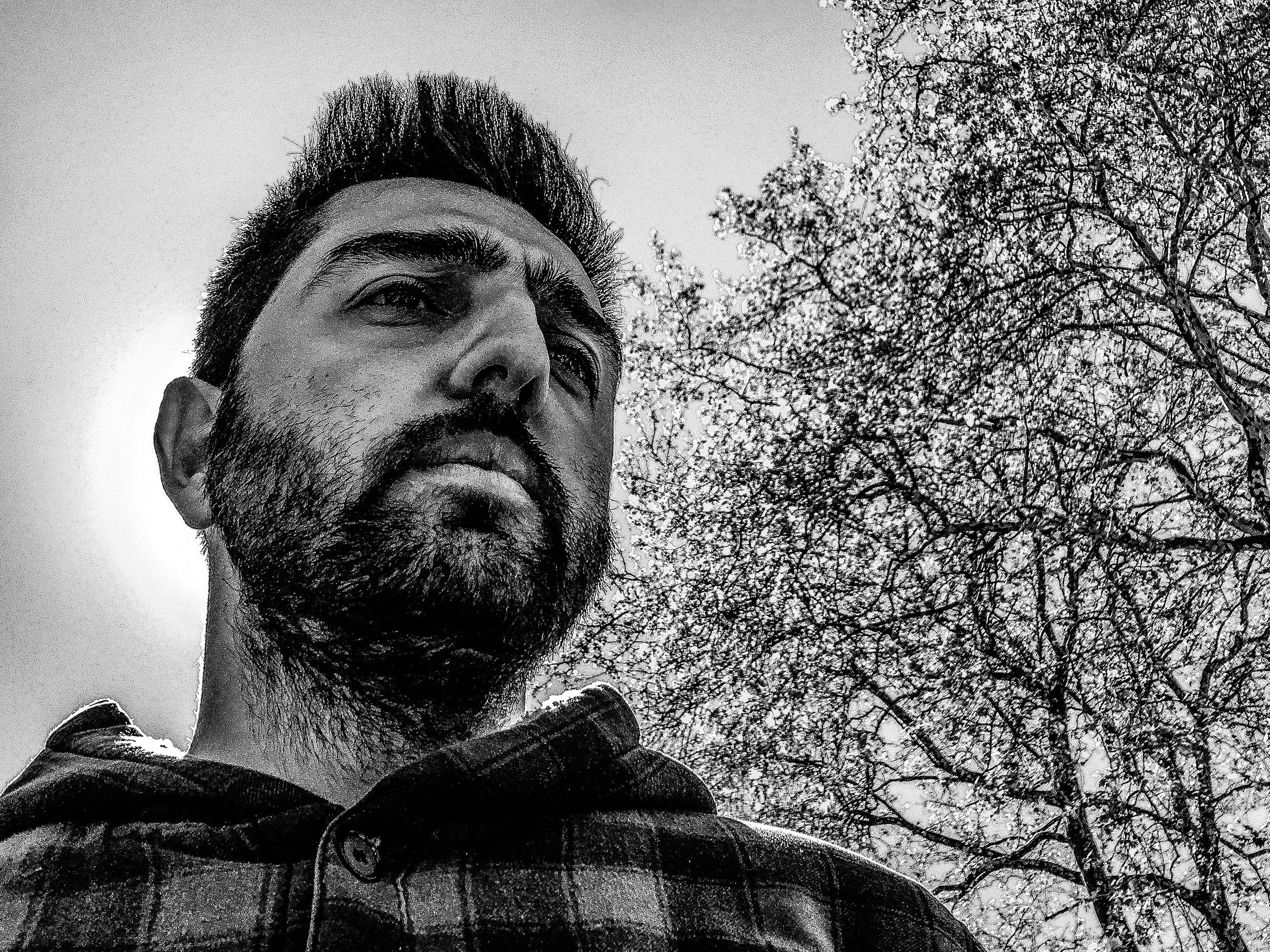 beard, low angle view, real people, one person, portrait, headshot, looking at camera, human face, outdoors, men, tree, clear sky, day, sky, one man only, young adult, close-up, adult, people