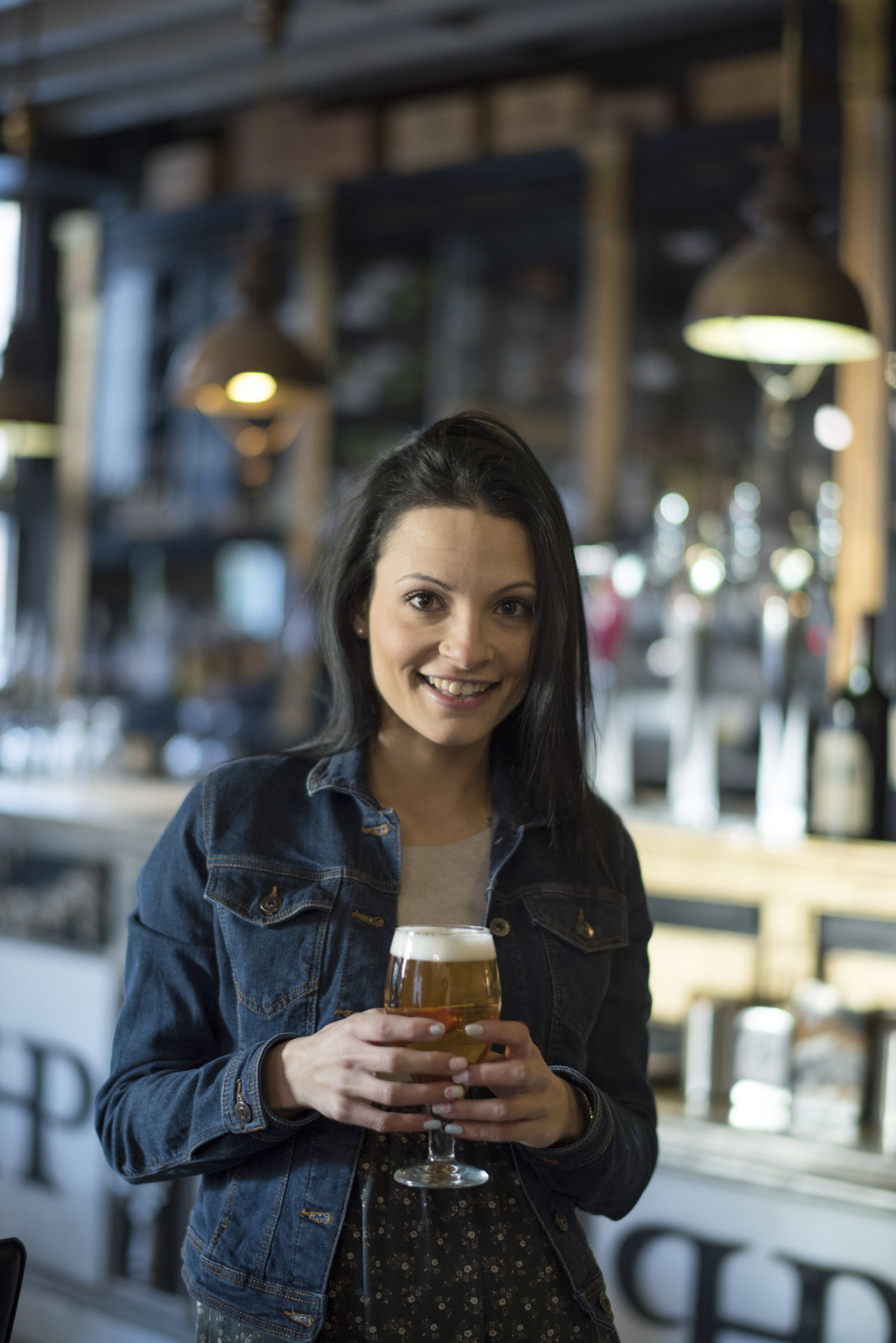 Alcohlday Alcohol Bar Beer Beer Glass Casual Clothing Drink Drinking Focus On Foreground Food And Drink Front View Happiness Happy Looking At Camera One Person People Portrait Real People Refreshment Restaurant Smiling Standing Woman Woman Portrait Young Adult