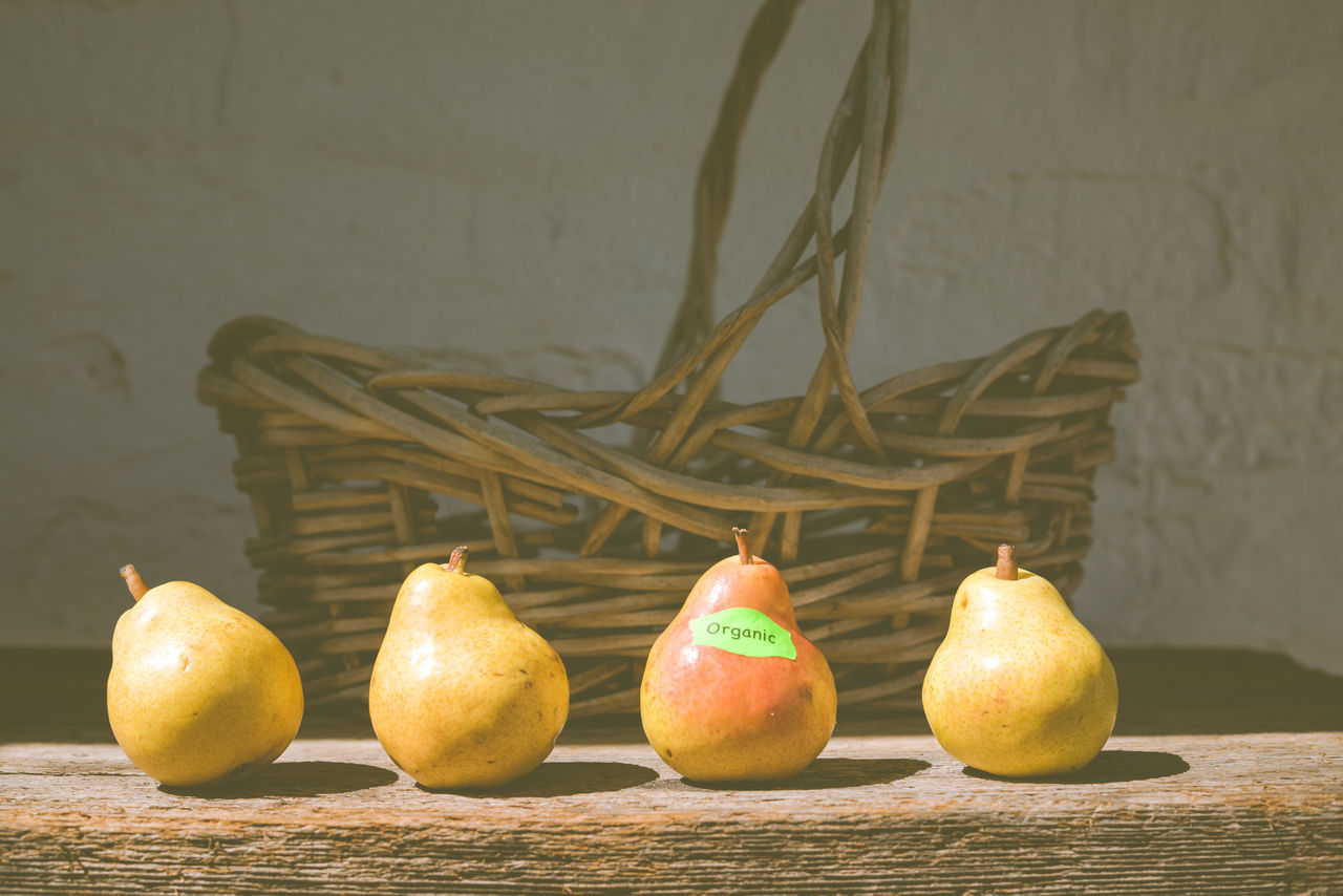 Four pears in front of a basket, one has an organic label attached. Apple Apple - Fruit Banana Citrus Fruit Close-up Diet Focus On Foreground Fodie Food Food And Drink Food Photography Foodphotography Foodporn Freshness Healthy Eating Lemon Matte No People Orange Color Organic Pears Ripe Still Life Still Life Photography