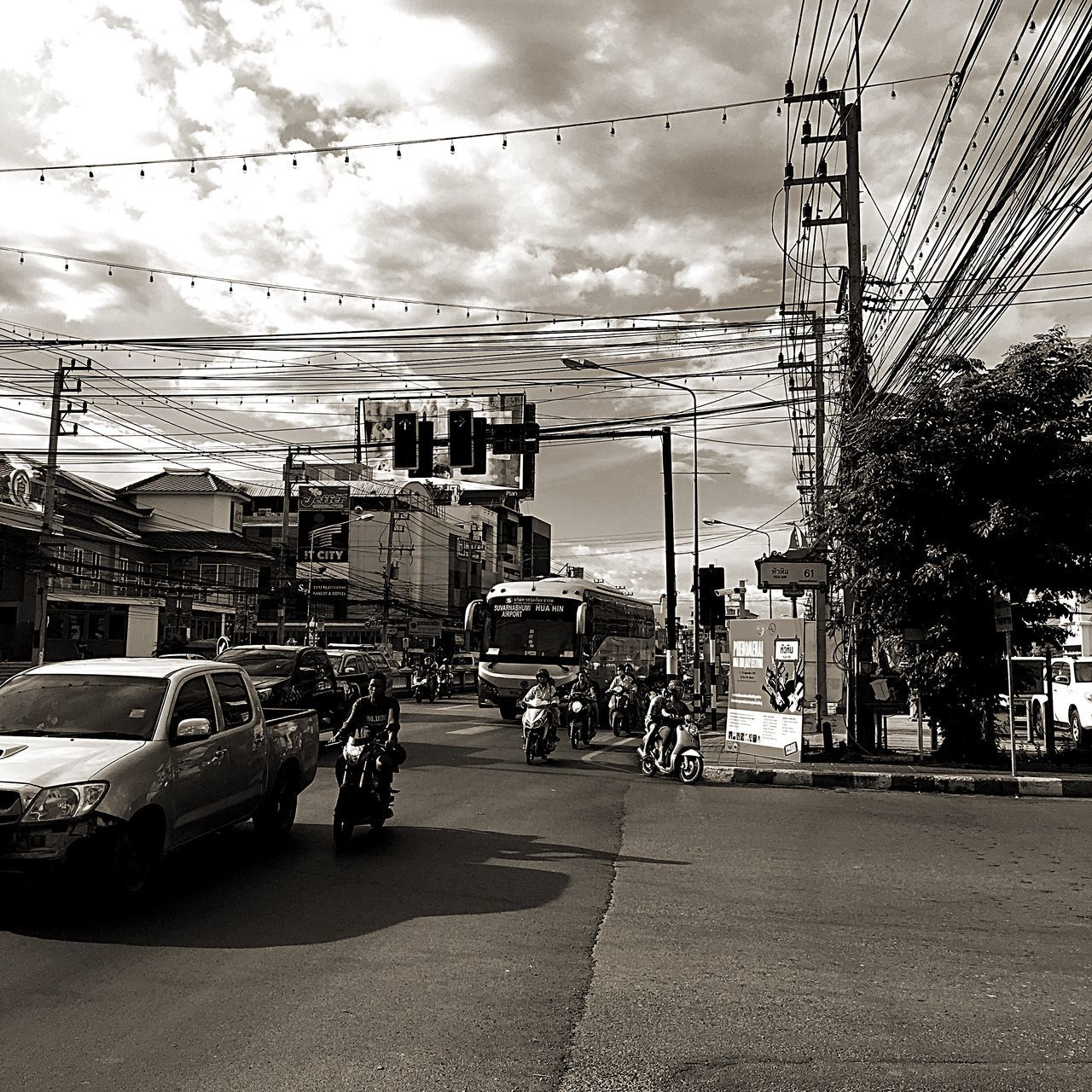 cable, transportation, car, sky, building exterior, architecture, built structure, street, road, power line, cloud - sky, mode of transport, land vehicle, electricity pylon, outdoors, city, day, city life, electricity, tree, telephone line, technology, nature, no people