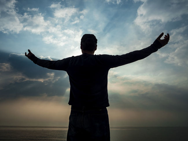 Arms Outstretched Arms Raised Beauty In Nature Cloud - Sky Day Gesturing Horizon Over Water Lifestyles Men Nature One Person Outdoors Real People Rear View Scenics Sea Silhouette Sky Standing Sunset Tranquil Scene Water