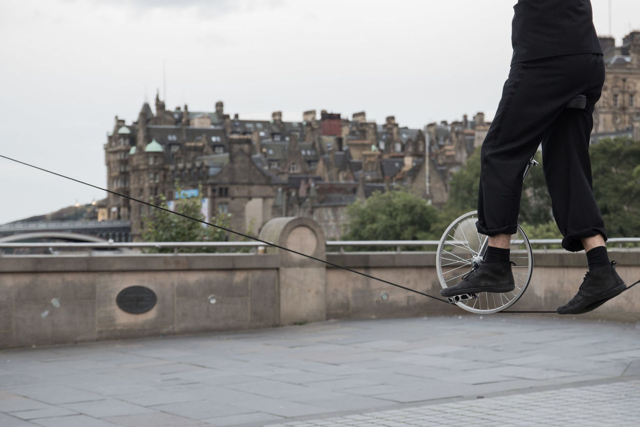 Street performer on a unicyle on a wire in Edinburgh during The Fringe festival Artistic Low Angle View Silhouette Street Performance Street Artist Unicycle Day High Wire Leisure Activity Outdoors Real People Street Performer Unicyclist