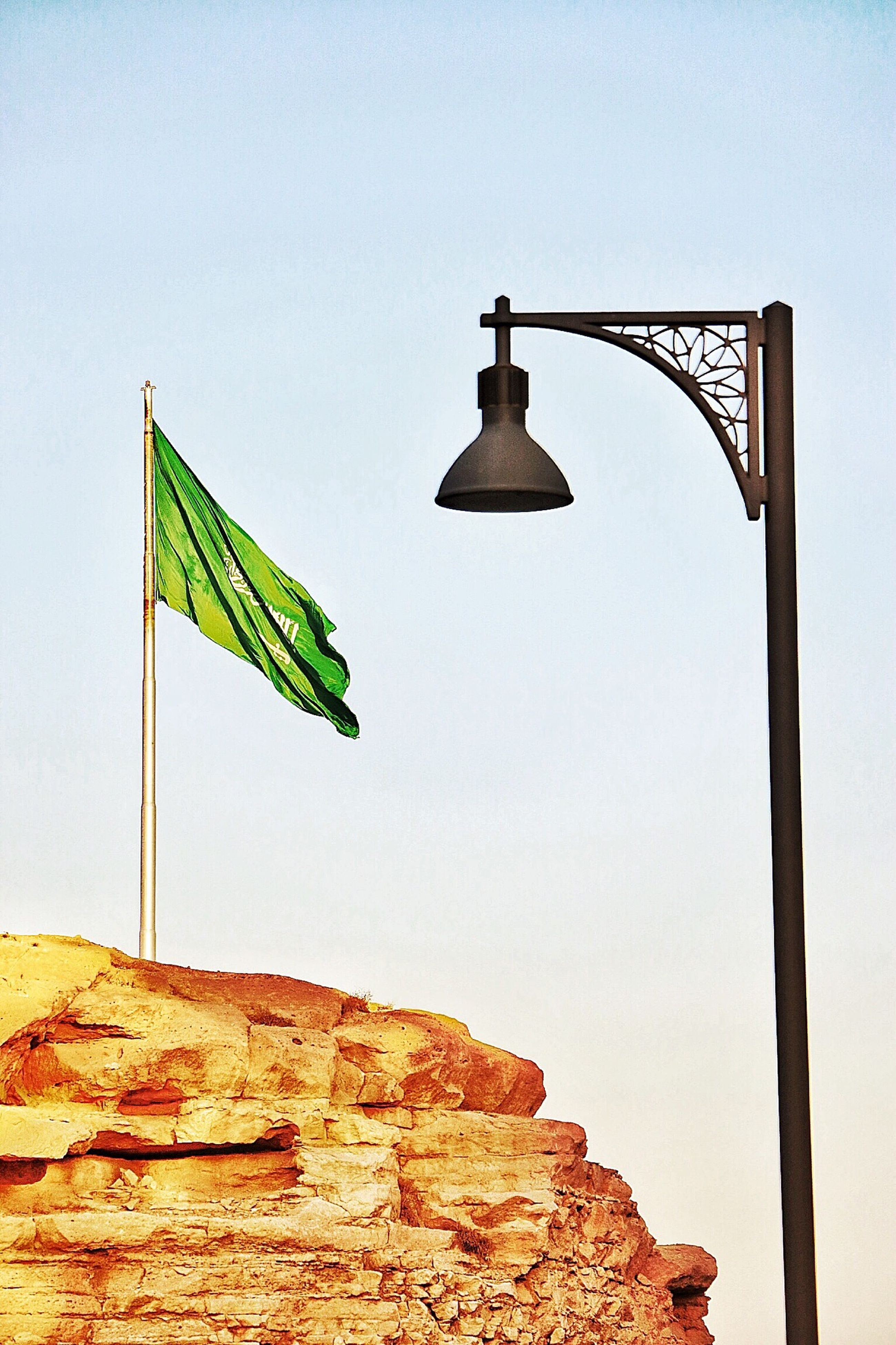 low angle view, clear sky, copy space, guidance, blue, flag, communication, day, sky, no people, direction, cross, nature, outdoors, tranquility, religion, rock - object, sunlight, pole, text