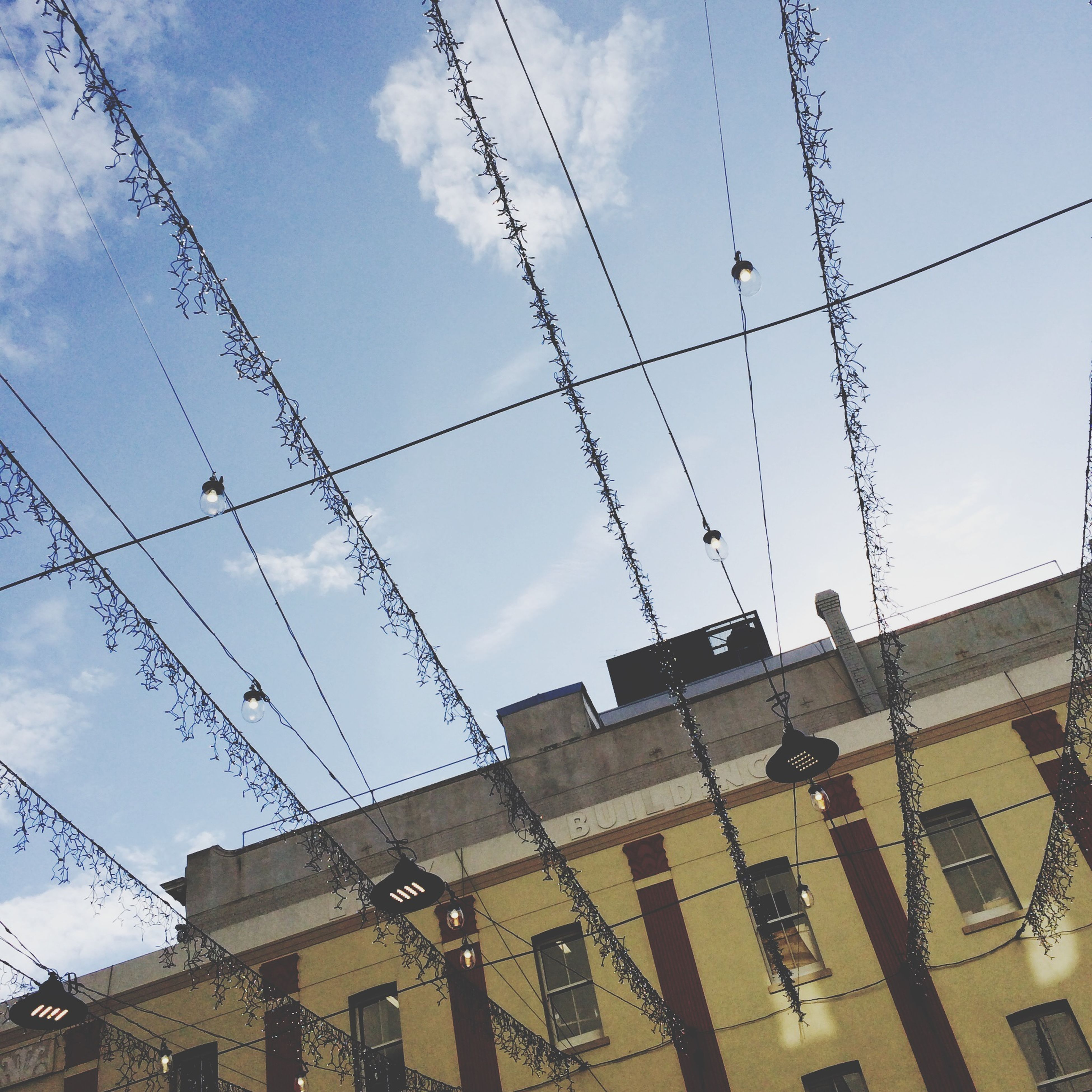 low angle view, power line, architecture, building exterior, built structure, cable, sky, electricity, power supply, electricity pylon, connection, building, power cable, residential building, cloud, city, cloud - sky, outdoors, day, no people
