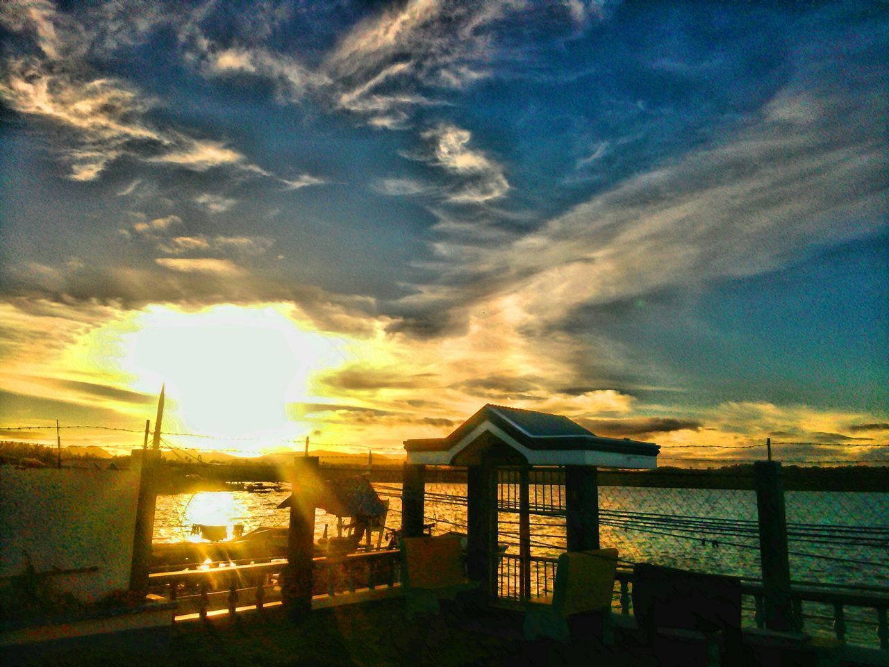 sky, sunset, cloud - sky, water, sea, no people, sunlight, nature, outdoors, tranquility, built structure, scenics, sun, beauty in nature, tranquil scene, horizon over water, architecture, beach, building exterior, day