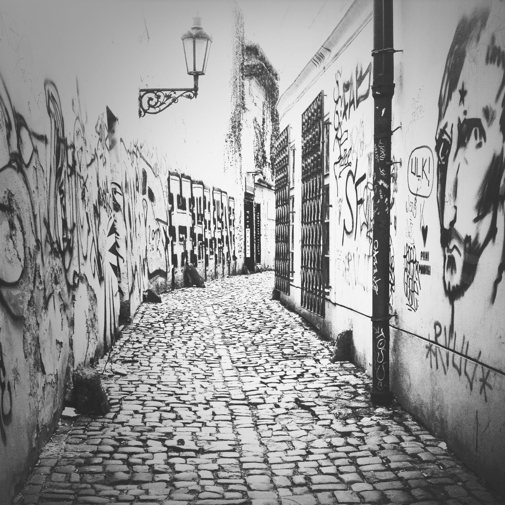 graffiti, architecture, built structure, wall - building feature, the way forward, art, art and craft, text, creativity, wall, indoors, diminishing perspective, cobblestone, building exterior, western script, walkway, no people, day, building, brick wall