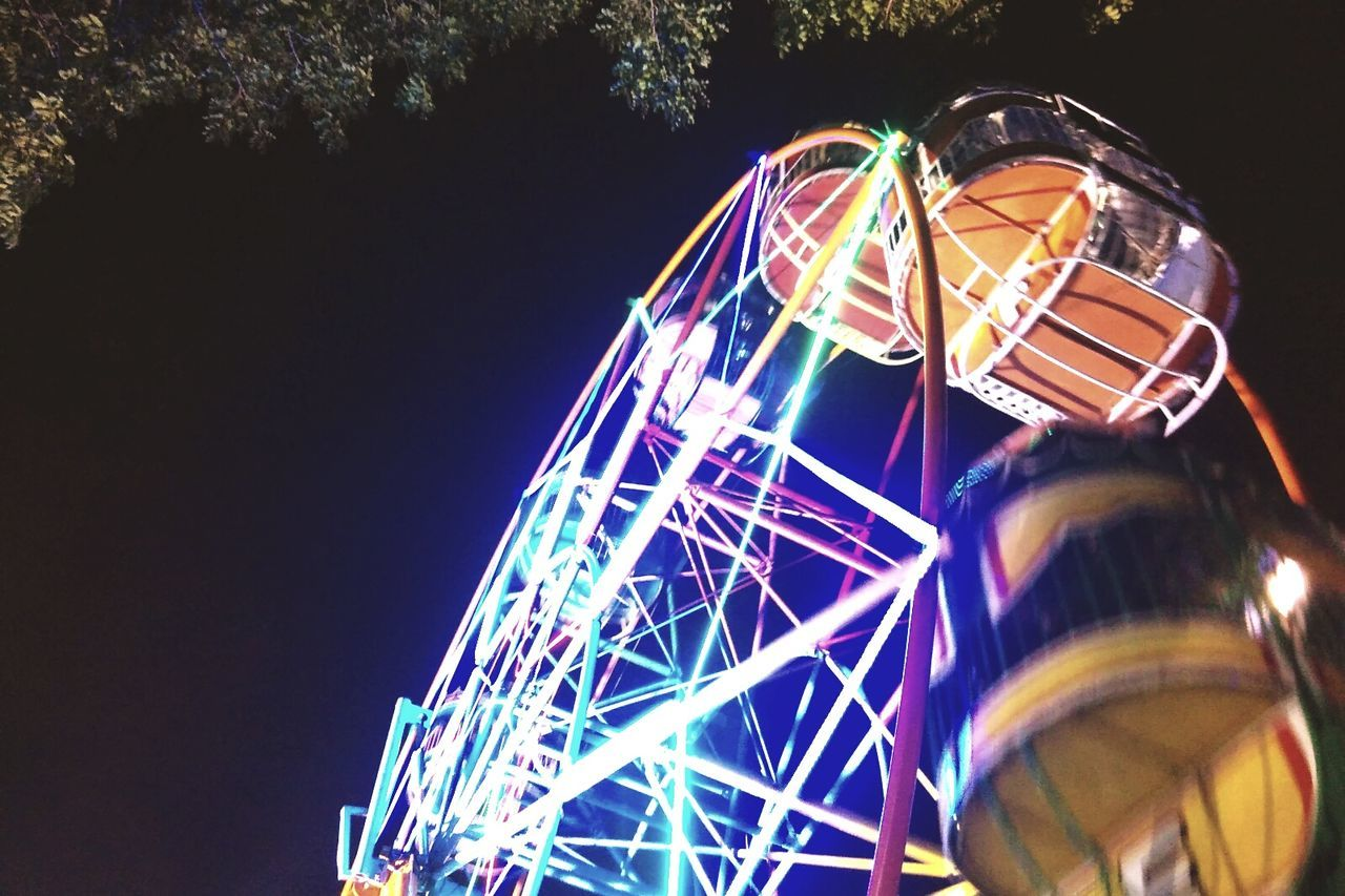amusement park, arts culture and entertainment, illuminated, night, ferris wheel, low angle view, amusement park ride, multi colored, outdoors, clear sky, no people, big wheel, black background, sky, close-up