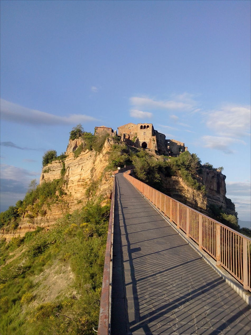 Ancient Architecture Blue Sky Bridge - Man Made Structure Built Structure Civita Di Bagnoregio Cloudy Sky Diminishing Perspective Handrails Narrow On Top Of A Mountain Pavement Shadows & Lights The City That Is Dying The Way Forward Tuff Tufo Under The Sun Vegetation World Monuments Watch