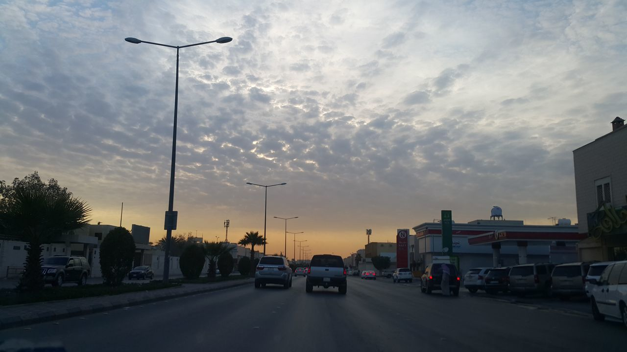 car, street light, land vehicle, cloud - sky, sky, transportation, mode of transport, sunset, road, street, outdoors, no people, tree, city, day
