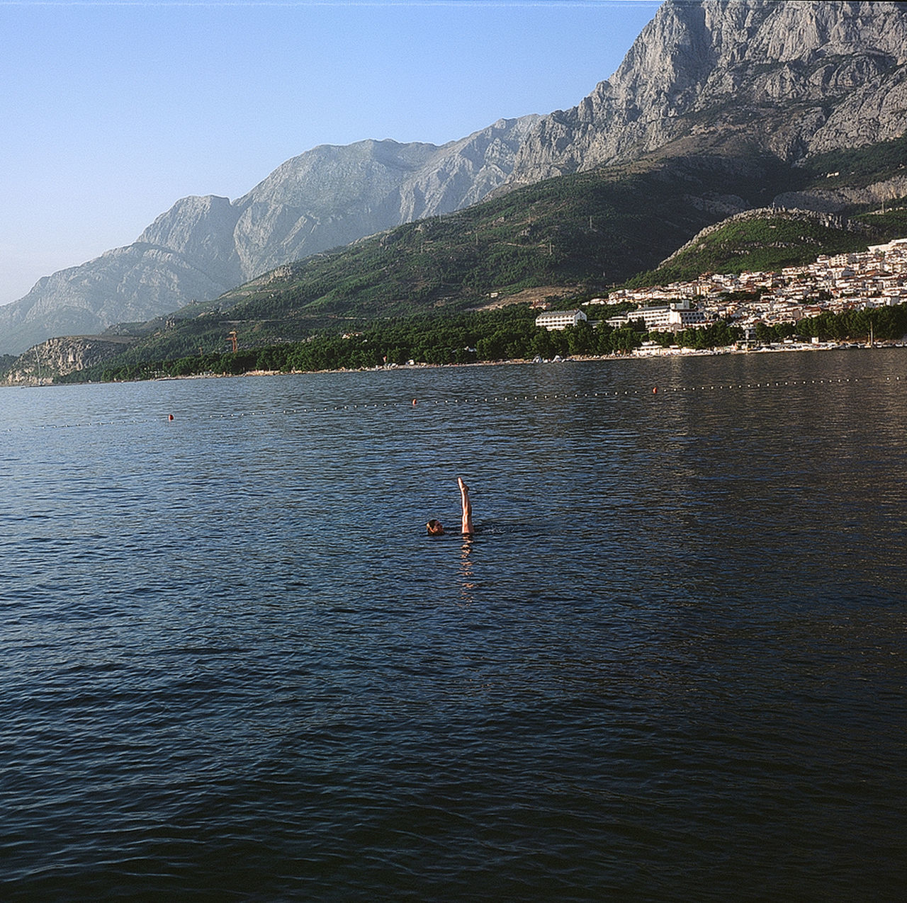 mountain, nature, real people, day, water, beauty in nature, waterfront, scenics, leisure activity, lake, mountain range, outdoors, lifestyles, one person, men, clear sky, paddleboarding, sky, people