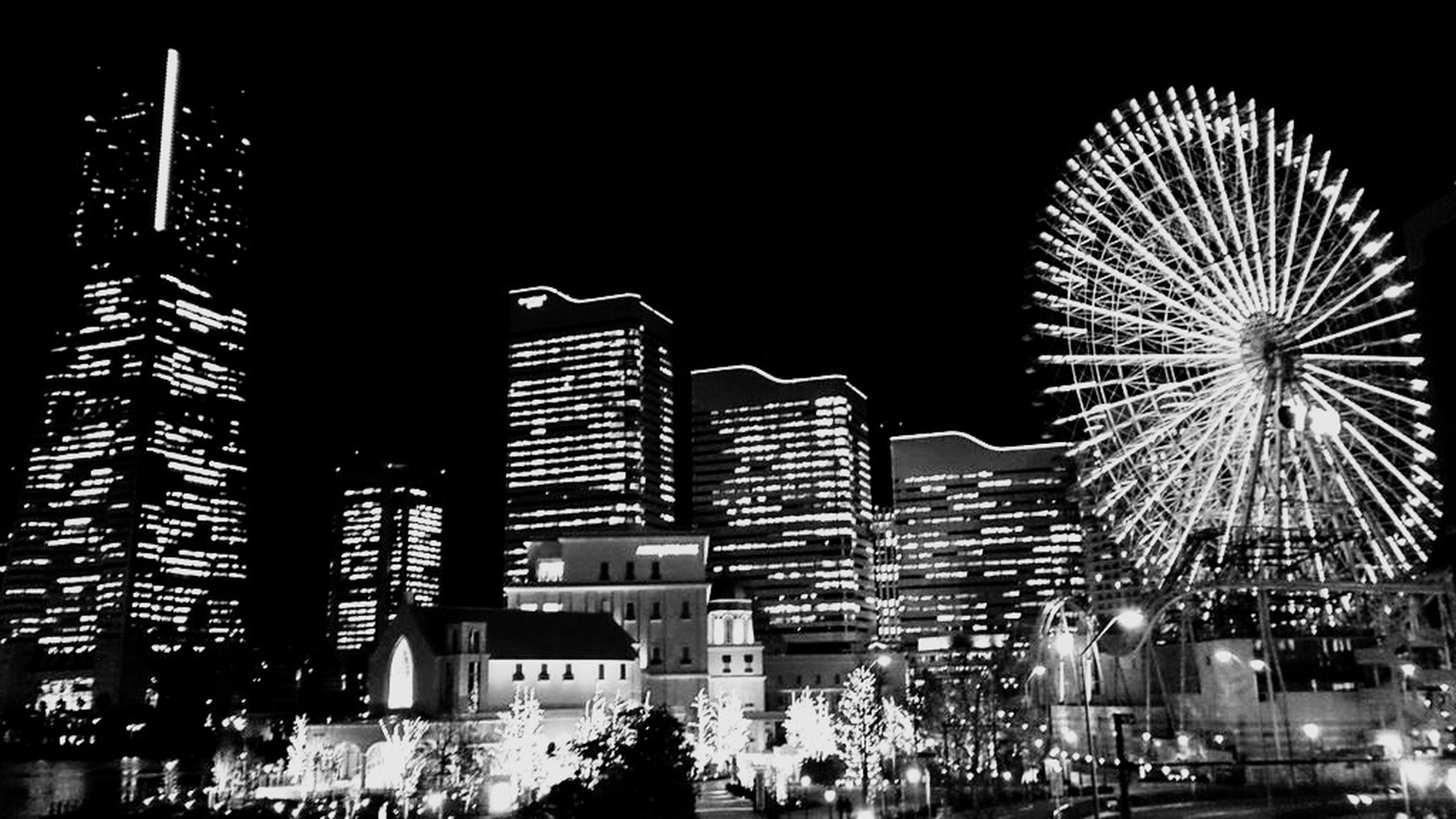 illuminated, night, architecture, built structure, building exterior, ferris wheel, low angle view, arts culture and entertainment, amusement park, city, amusement park ride, clear sky, sky, outdoors, lighting equipment, incidental people, modern, city life, no people, tall - high