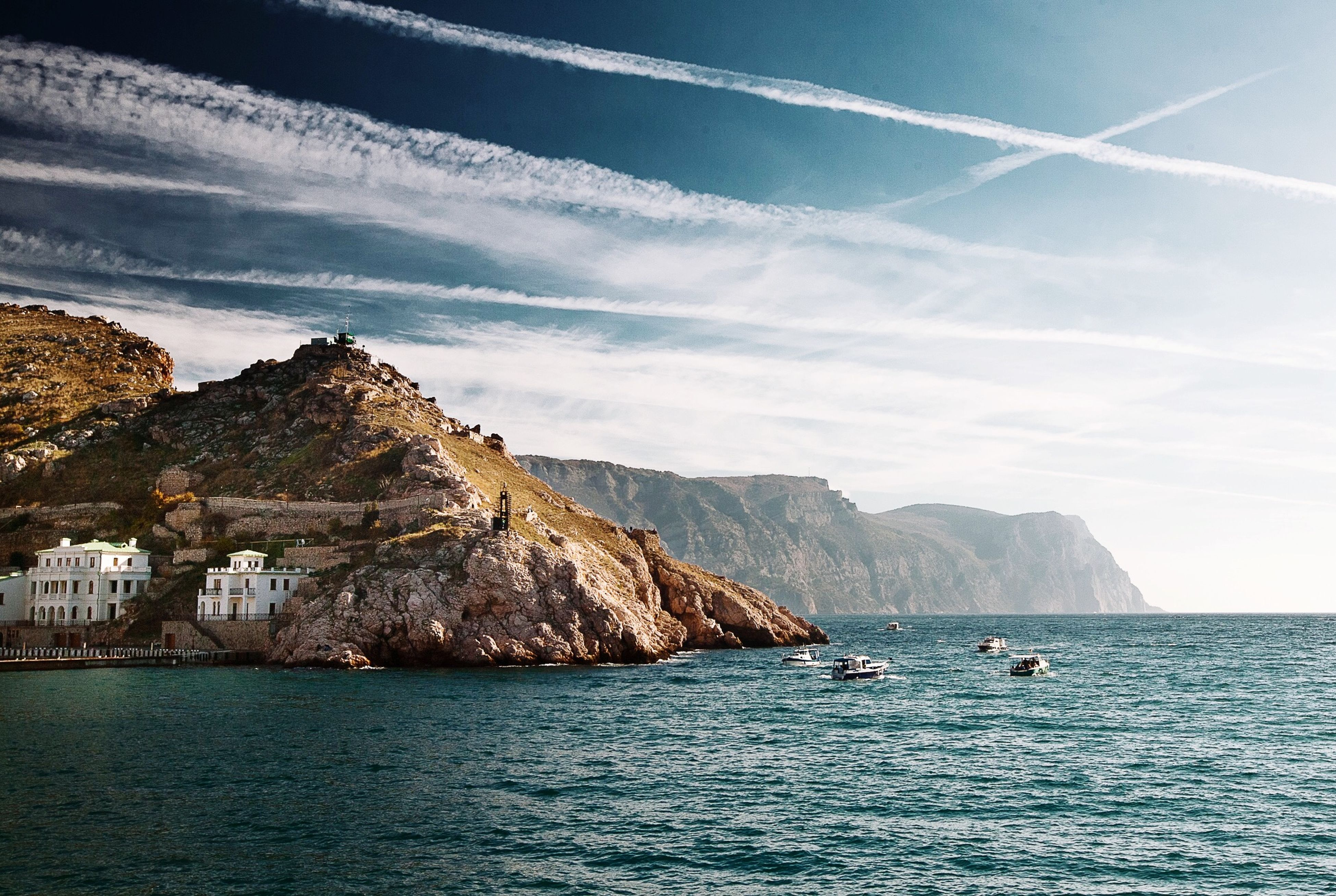 sea, water, mountain, waterfront, sky, nautical vessel, scenics, transportation, mountain range, tranquil scene, beauty in nature, tranquility, boat, mode of transport, nature, cloud - sky, cloud, rippled, blue, rock formation