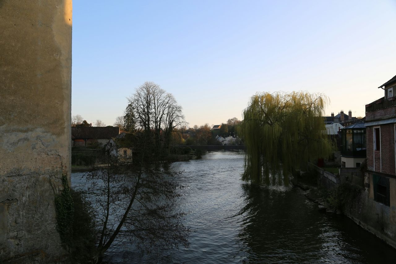 River And Houses Against Clear Blue Sky At Sunset