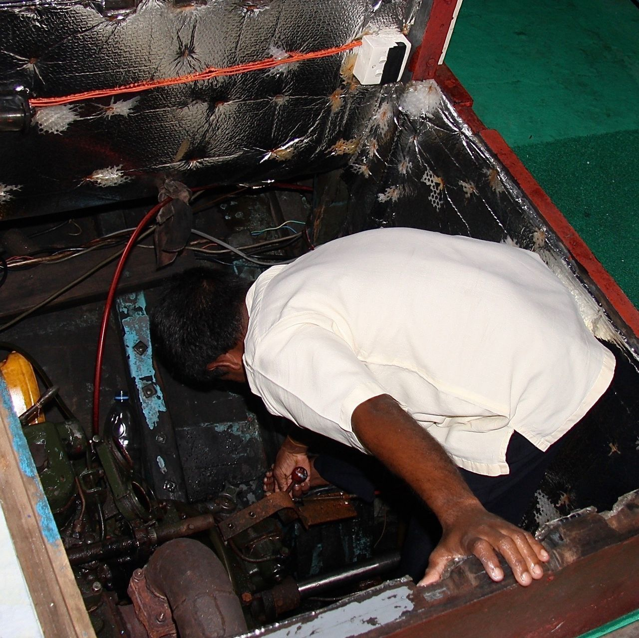 Skipper looking at Motor in traditional Dhoni Boat Outdoors Manual Worker Repairing Working People One Man Only Dhoni Traditional Boat Business Sea Travel Maldives Environment Indian Ocean Colors Technology Motor Journey Transportation Design Man People And Places