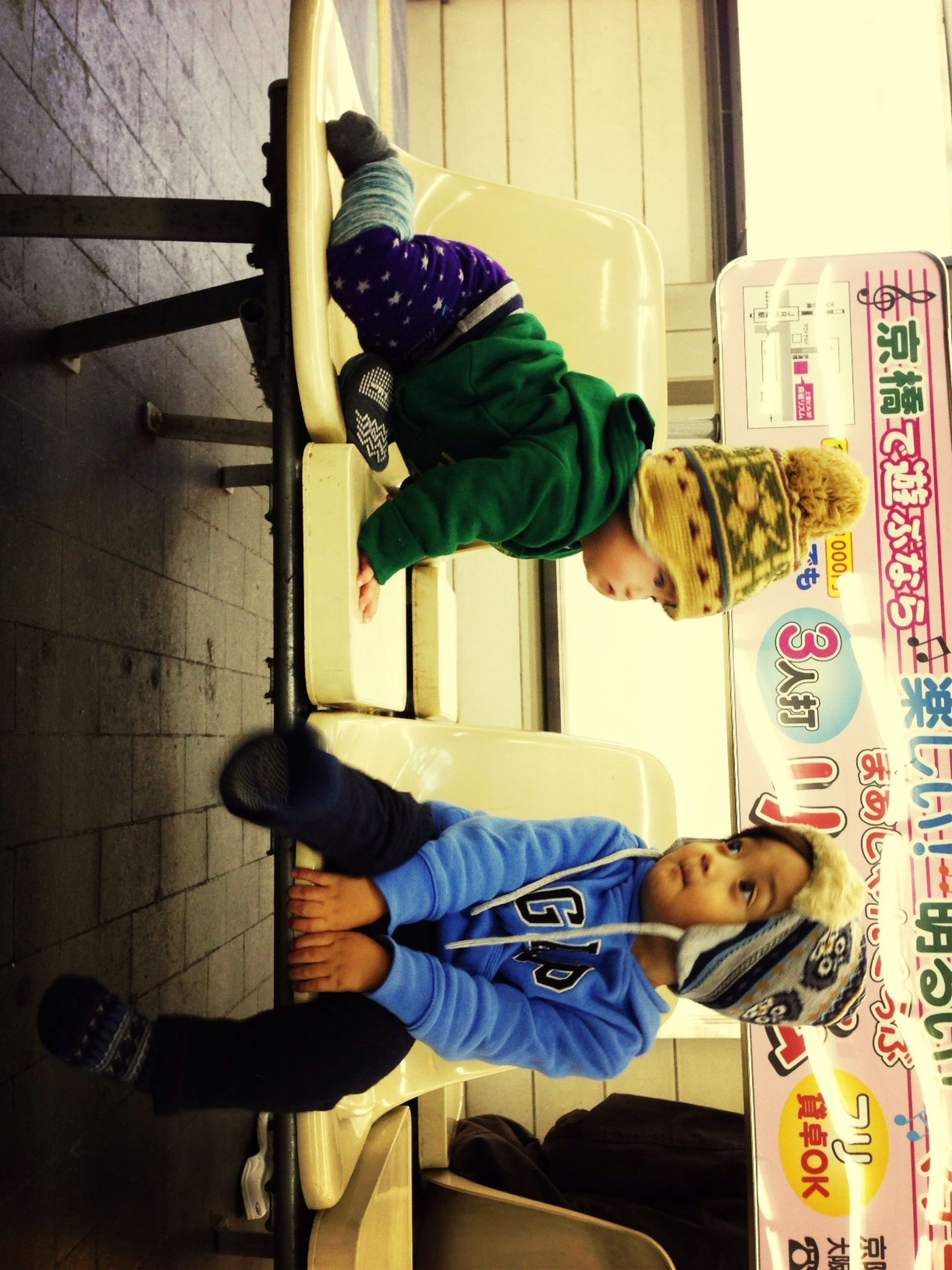 casual clothing, lifestyles, full length, person, sitting, leisure activity, togetherness, indoors, boys, front view, childhood, three quarter length, bonding, young men, communication, standing, happiness