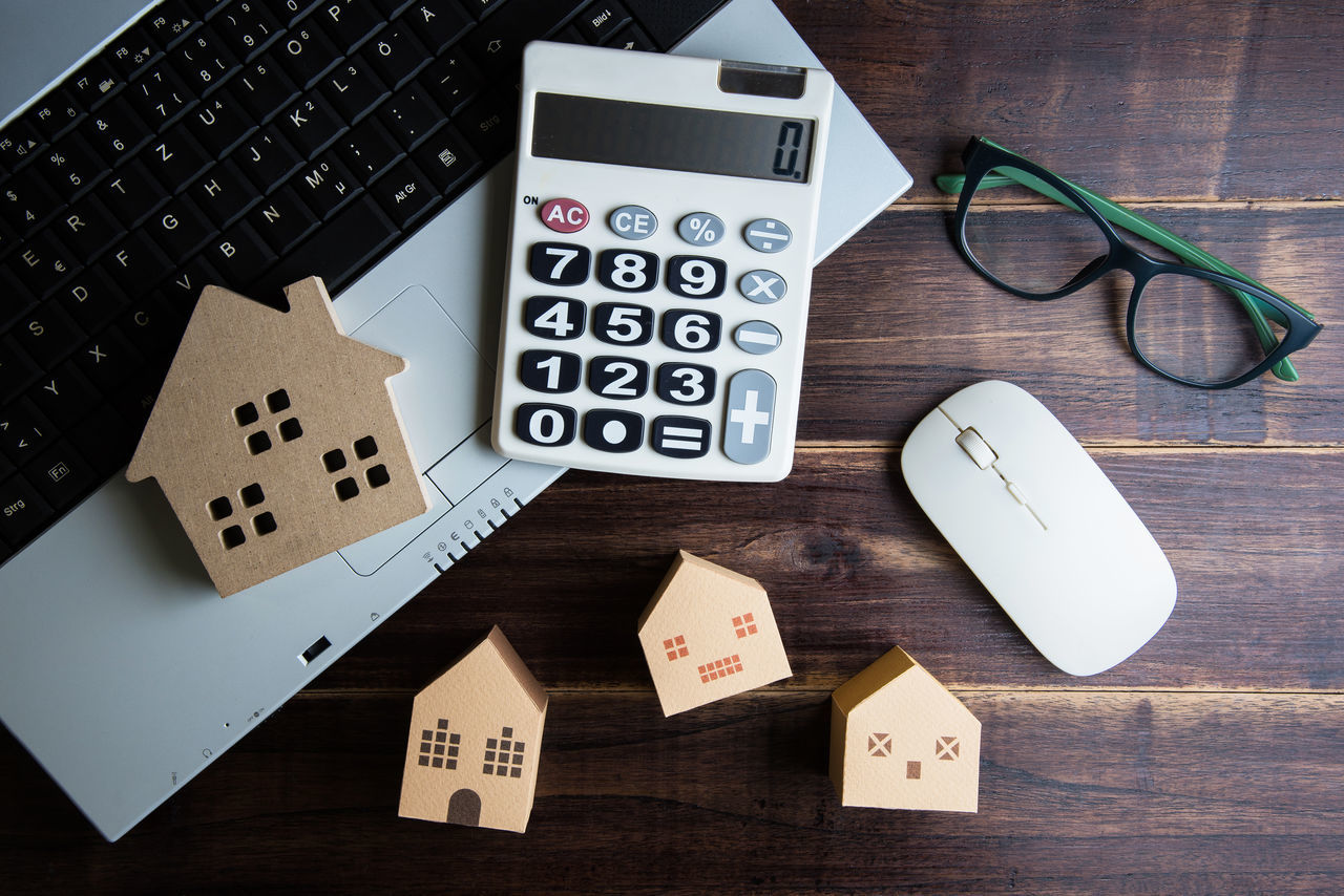 Wooden house, paper house, calculator, glasses and Laptop note book on wooden table background with copy space.Real estate concept, New house concept, Finance loan business concept. Computer Computer Keyboard Connection Day Digital Tablet Gambling Gambling Chip Indoors  Luck No People Technology Wireless Technology