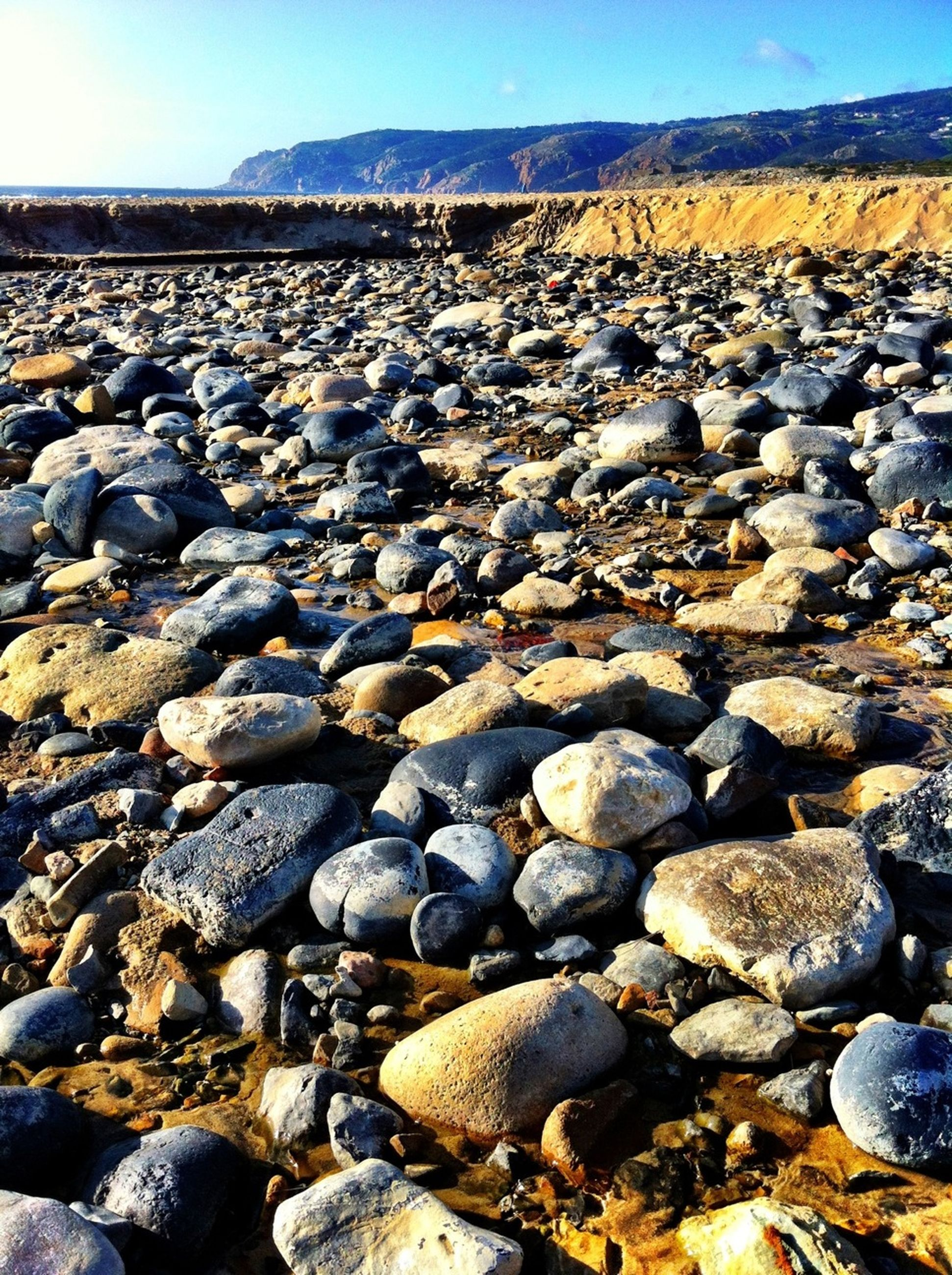 stone - object, pebble, abundance, tranquil scene, tranquility, nature, rock - object, stone, sky, landscape, large group of objects, scenics, surface level, beauty in nature, beach, stack, rock, sunlight, outdoors, day