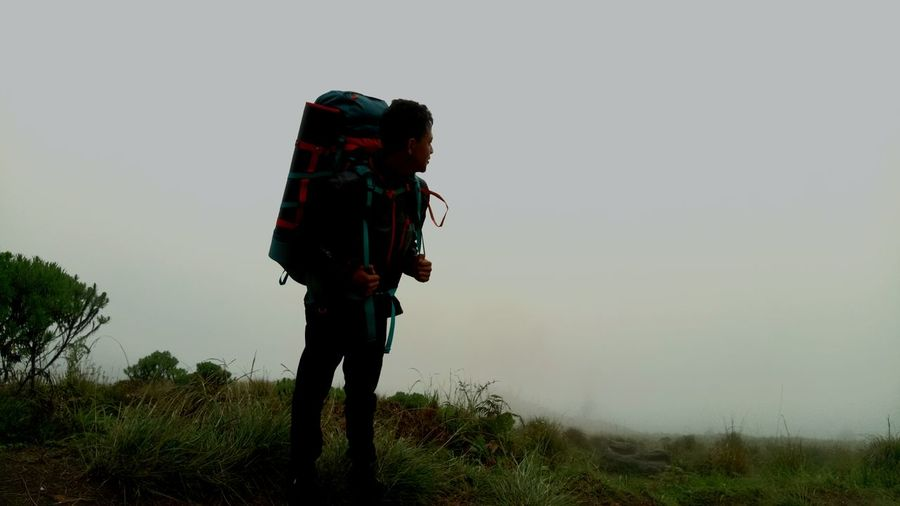 One Man Only One Person Only Men Backpack Adult People Day Adults Only Hiking Holding Outdoors Full Length Men Adventure Grass Camera - Photographic Equipment Nature Musician Sky Close-up Beauty In Nature Landscape Cloud - Sky Silhouette