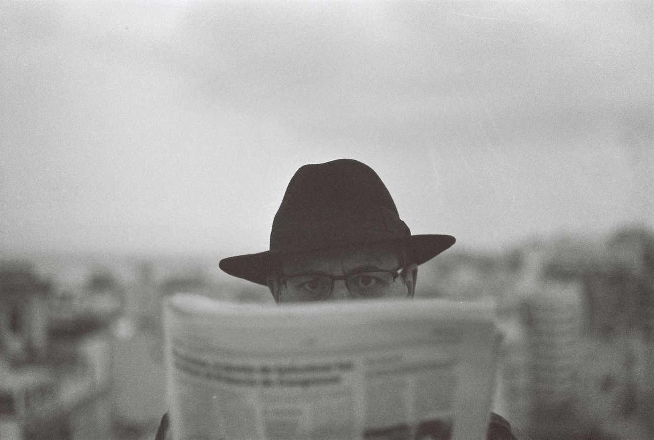 What's the world coming to? (analog version - Leica M7) Portrait Portrait Of A Man  Portrait Of A Friend Black And White Portrait Blackandwhite Monochrome Front View Headshot Hat Eyeglasses  Glasses Newspaper The Portraitist - 2017 EyeEm Awards Film 35mm Film Photography The Film Files