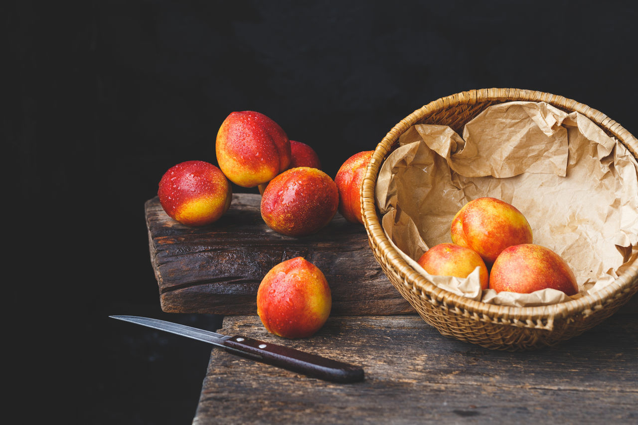 High Angle View Of Wet Peaches With Knife And Basket On Wooden Table Against Black Background