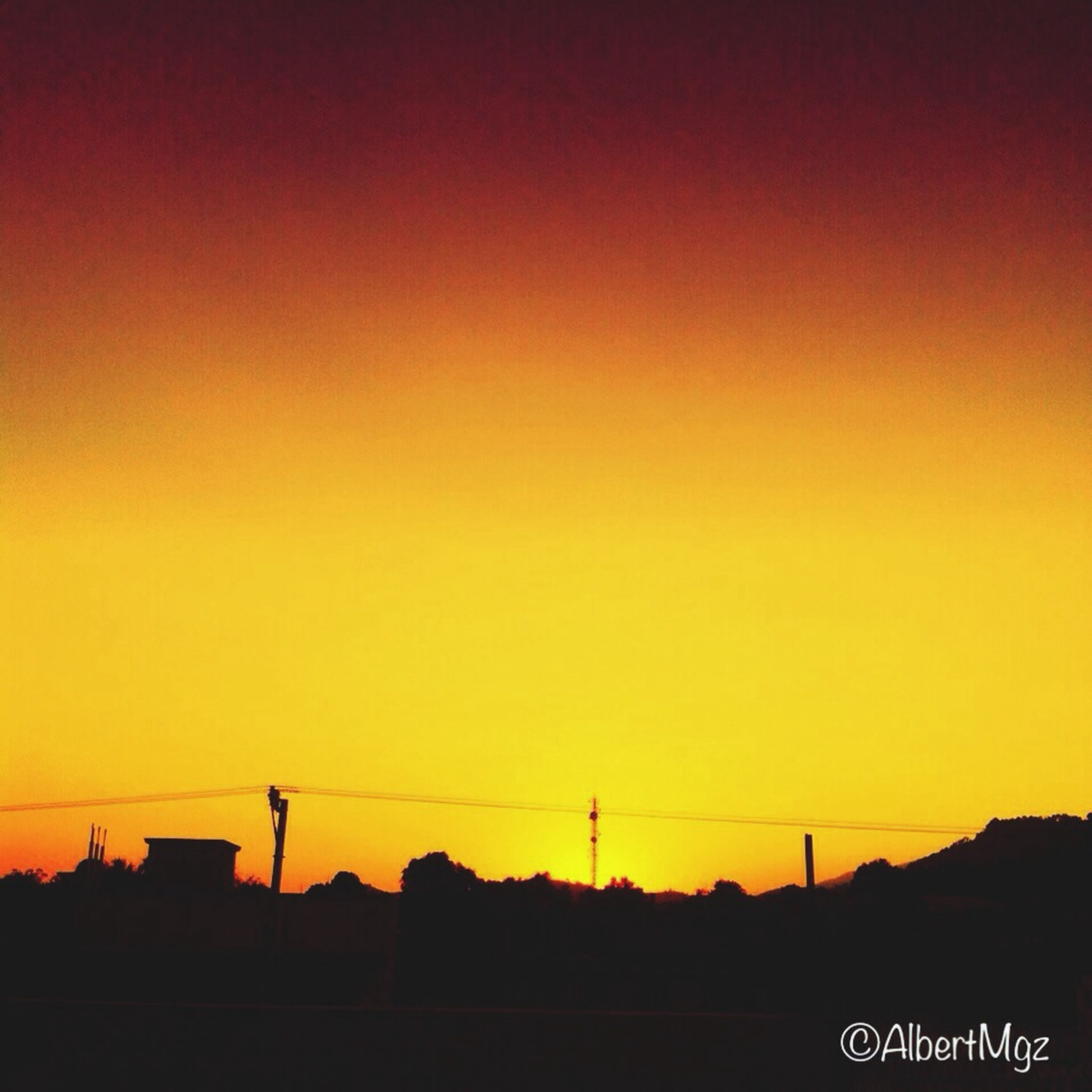 sunset, silhouette, orange color, copy space, clear sky, connection, electricity pylon, scenics, beauty in nature, built structure, nature, power line, tranquility, outdoors, tranquil scene, no people, architecture, dark, dusk, low angle view