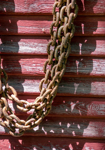 old rusty thick chain hang from a nail against a weathered red barn wall Barn Weathered Background Barn Wall Chain Close-up Connection Day Durability Metal No People Old Outdoors Rusty Shadow Steel Strength Strong Thick Tied Up Wood - Material