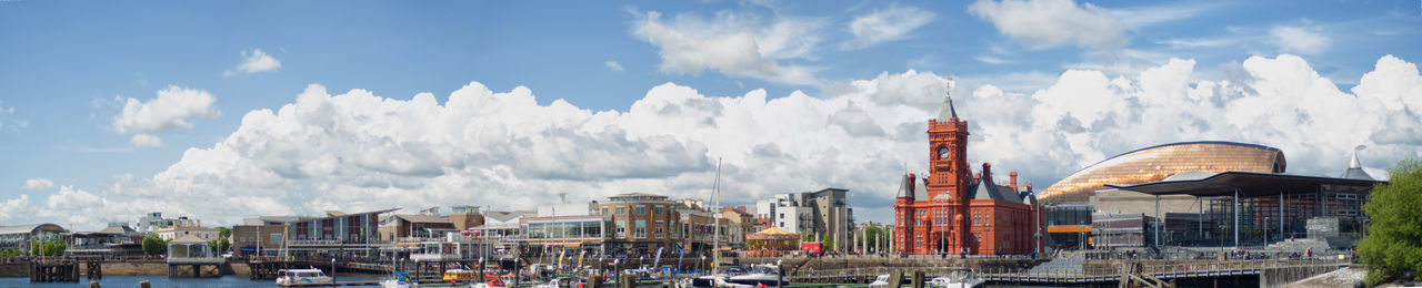 Panoramic View Of Buildings And Church By Harbor Against Cloudy Sky
