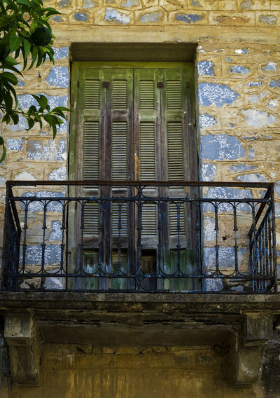 Old wrought iron balcony with closed wooden shutters. Wooden Shutters Abandoned Architecture Bad Condition Building Exterior Built Structure No People Window Wrought Iron Design
