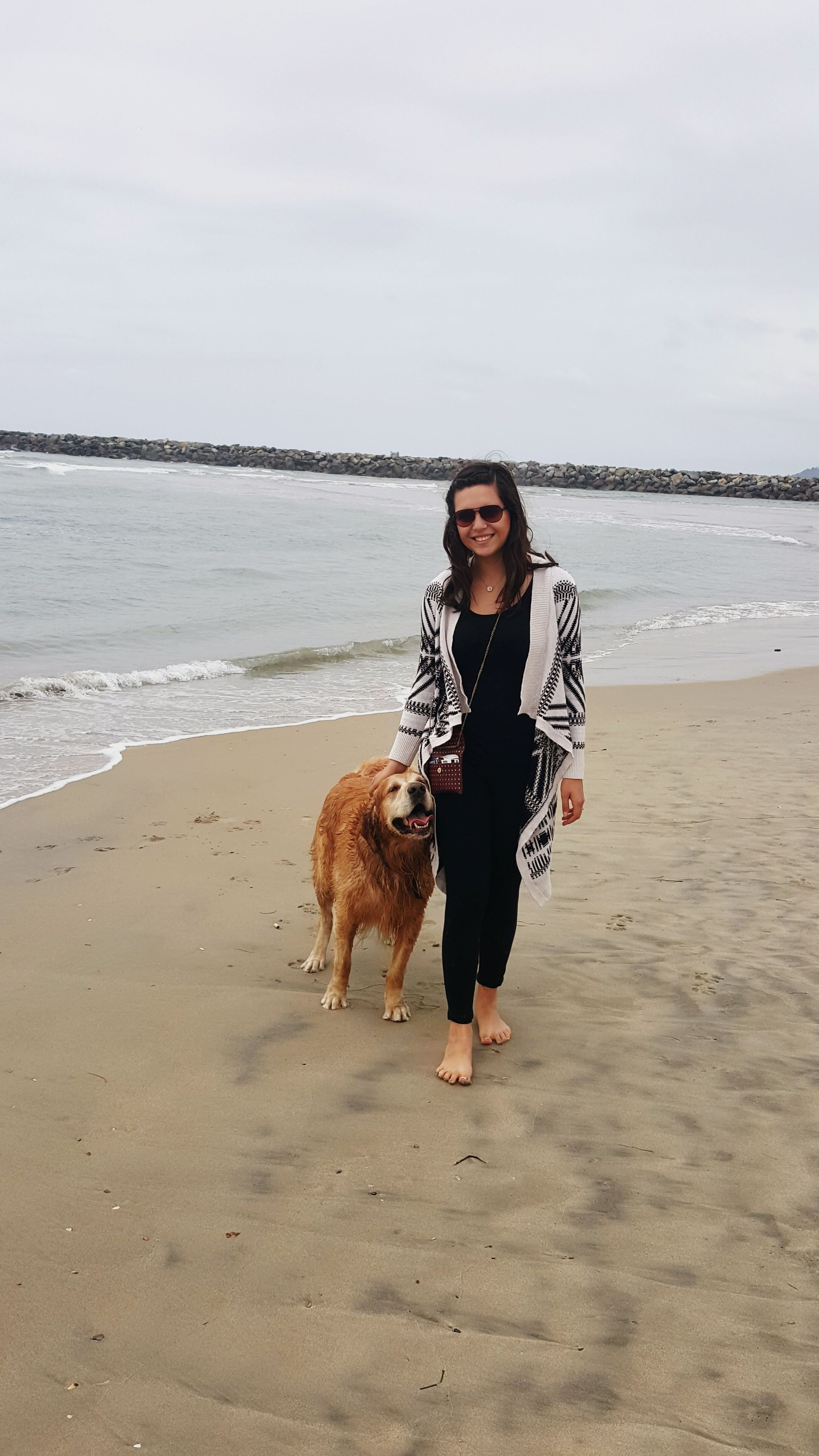 beach, portrait, sea, sand, looking at camera, shore, water, person, domestic animals, young adult, full length, lifestyles, leisure activity, dog, mammal, pets, animal themes, one animal